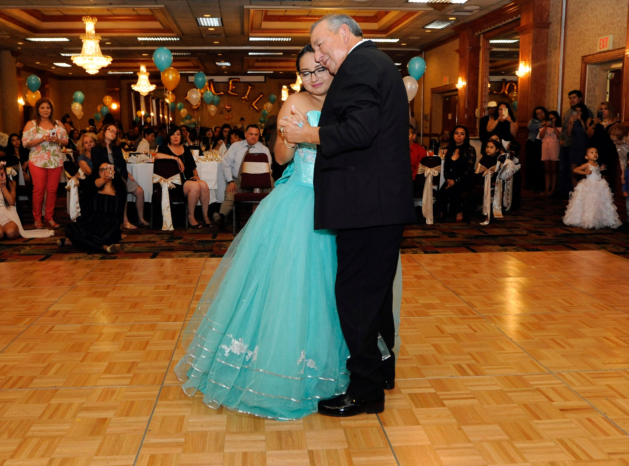 Soleil Garcia, left, dances with her grandfather, Jose, during her quinceañera reception, July 28, 2018 at the Holiday Inn in Southgate.  Jose was substituting for his son, Jorge Garcia, who was deported to Mexico in January.