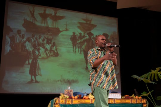 "Gregory McKenzie performs a song called the ""Middle Passage"" about slavery during the celebration of the first night of Kwanzaa at the Charles H. Wright Museum of African American History in Detroit on Dec. 26, 2018. (David Guralnick / The Detroit News)"