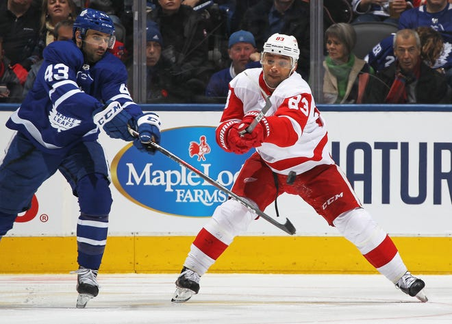Trevor Daley of the Detroit Red Wings, skating in his 1,000th NHL game, fires a pass against the Toronto Maple Leafs on Sunday.