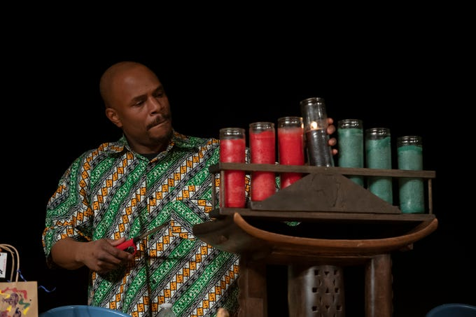 Gregory McKenzie, co-host of the event, lights the unity candle during a celebration of the first night of Kwanzaa, at the Charles H. Wright Museum of African American History, in Detroit, Dec. 26, 2018.