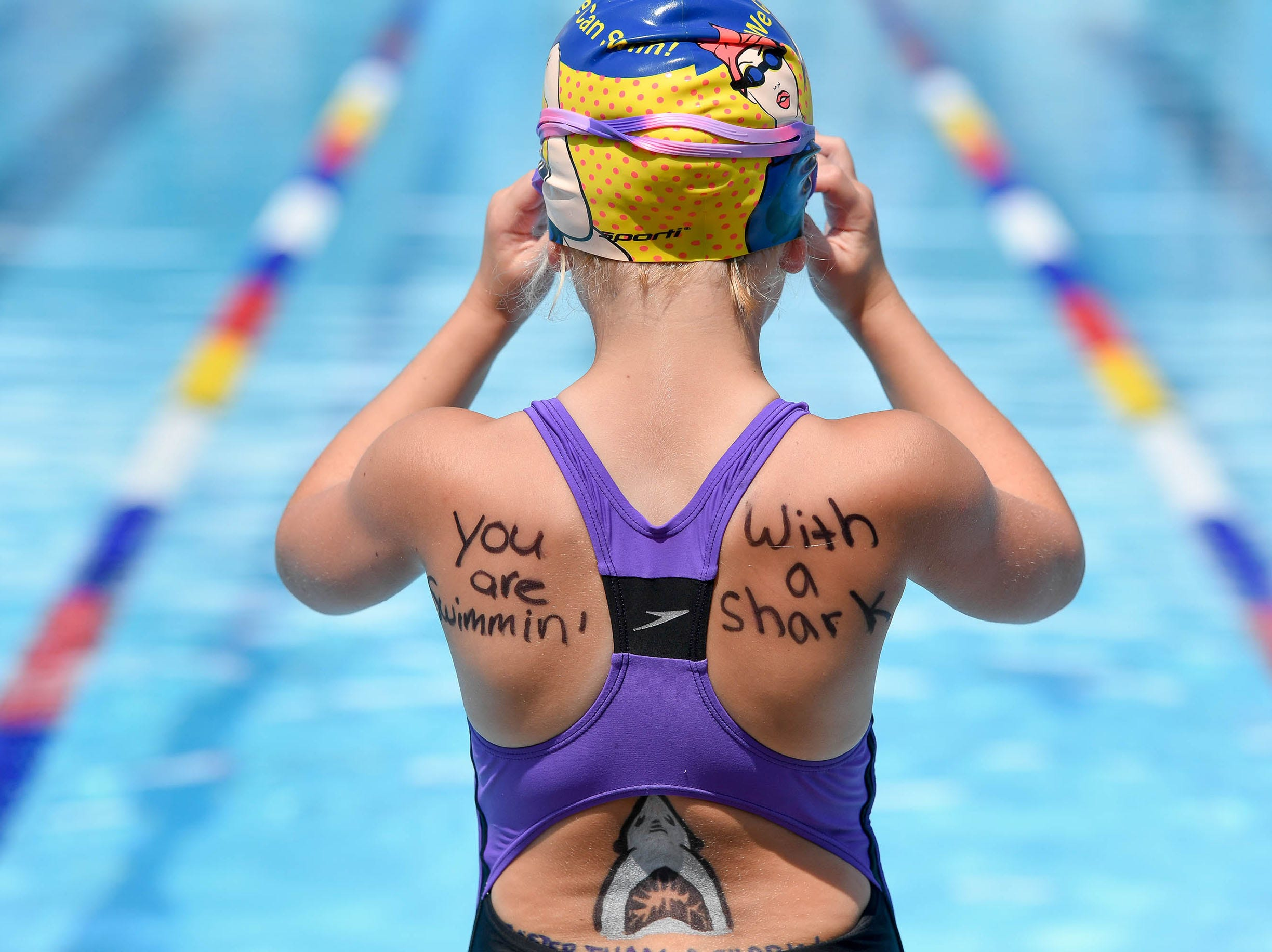 Paige Hoefling adjusts her goggles before the start of the 7-8 year-old 25 yard Butterfly during the 2018 City Swim Meet preliminaries held in Evansville's Garvin Park Saturday. The meet, with nearly 800 swimmers ages 4 to over 65-years-old, continues Sunday with the finals, July 14, 2018.