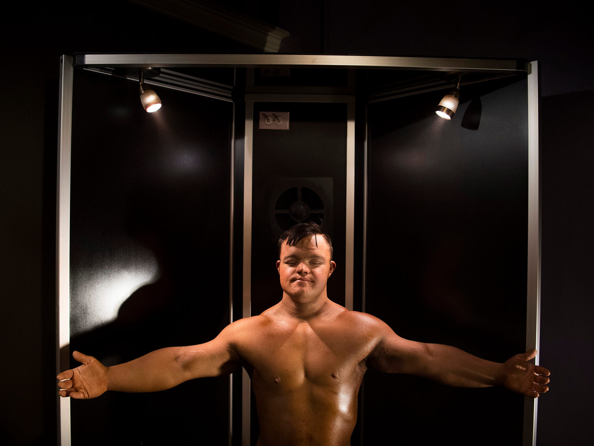 Collin Clarke receives the second coat of a spray tan applied by Shannon Tichenor, owner of Salon T in Newburgh, Ind., the day before his Indiana Muscle competition in March of 2018. No bodybuilder competes without a good spray tan which helps accentuate their muscles for the judges and audience as they compete.