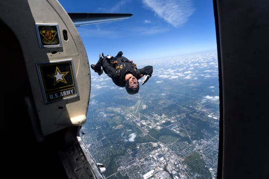 Staff Sgt. Dusty Gebhardt, a member of the United States Army Golden Knights parachute team, free falls towards downtown Evansville, Friday afternoon, June 29, 2018. The parachuting team practiced their routine of landing beside the Four Freedoms monument in preparation for the ShrinersFest Air Show, which will be held at 3 p.m. Saturday and 2 p.m. Sunday.