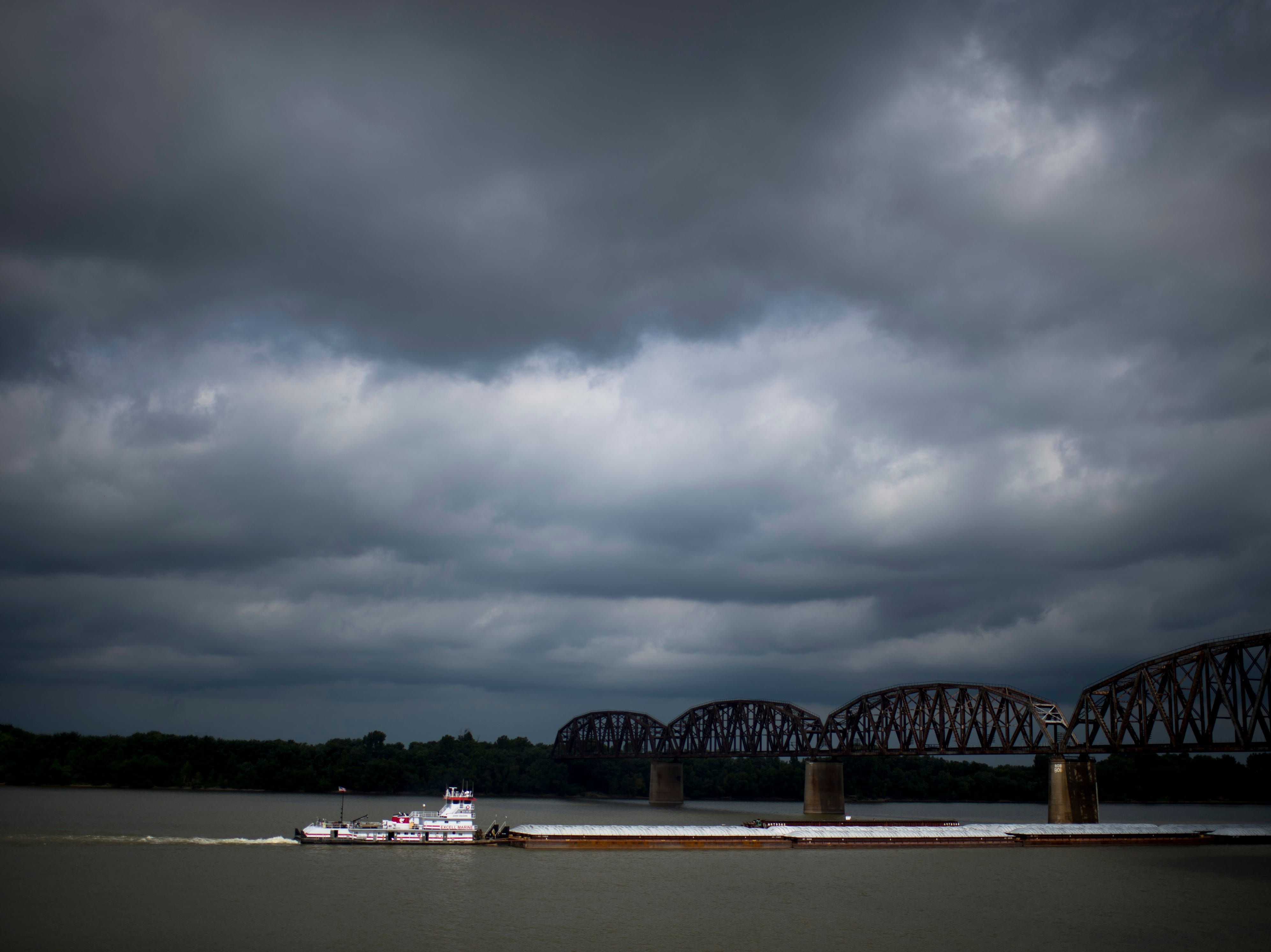 The John Vaughn out of Cave-In-Rock, Ill., moves its barges upriver on the Ohio River near Downtown Henderson, Ky., Wednesday morning.