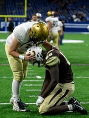 Bishop Dwenger's Grant Sorg (51) gives Central's Rayzel Joiner (88) a pat on the back following the Bears' 16-10 loss in the Class 4A state championship match which went into quadruple overtime at Lucas Oil Stadium in Indianapolis, Ind., Friday, Nov. 23, 2018.