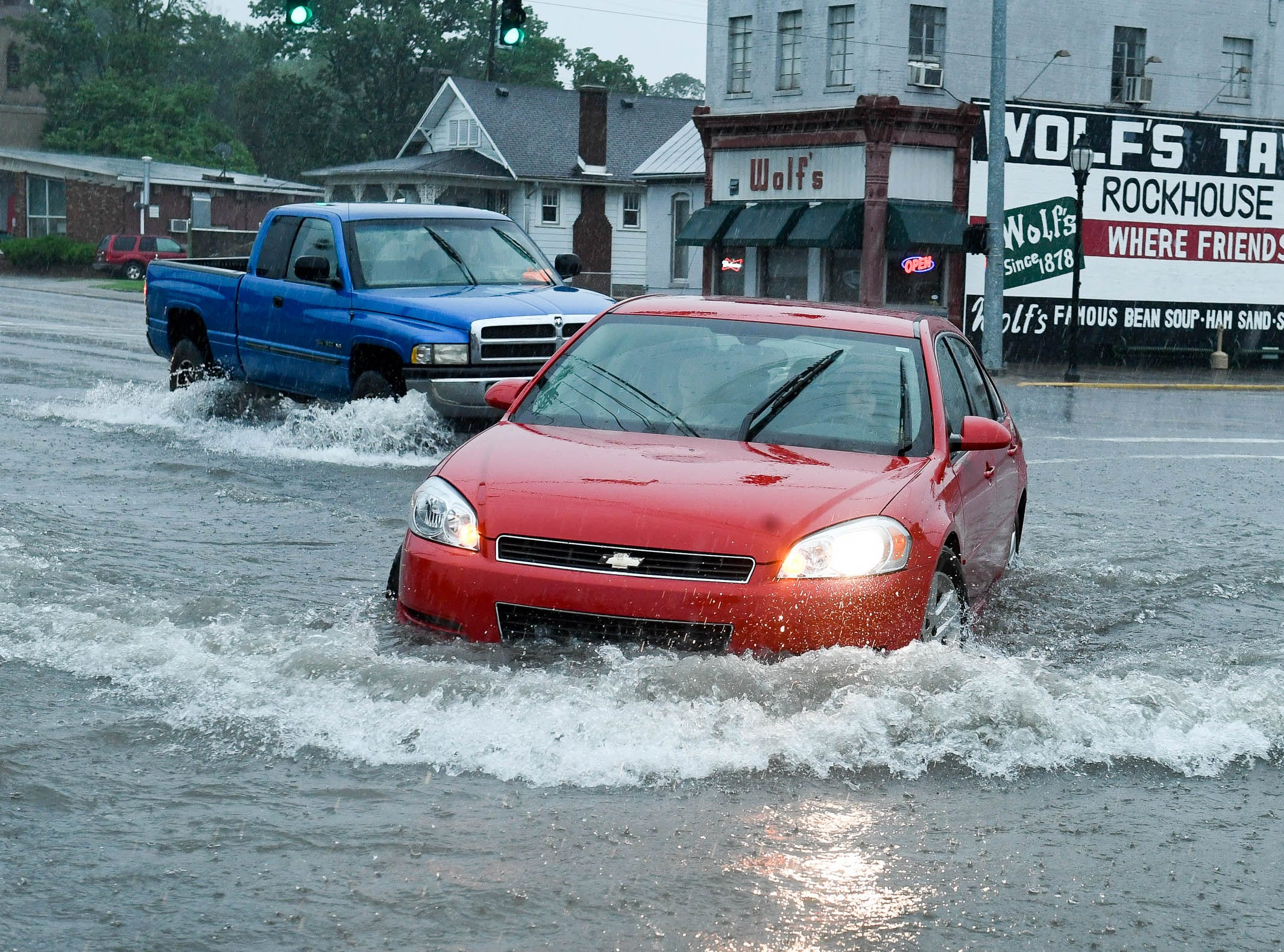 Traffic negotiates high water near the intersection of South Green and First Streets after a mid-day severe thunderstorm unleashed torrential rain and wind gusts reportedly near sixty miles per hour on downtown Henderson Thursday, May 31, 2018.