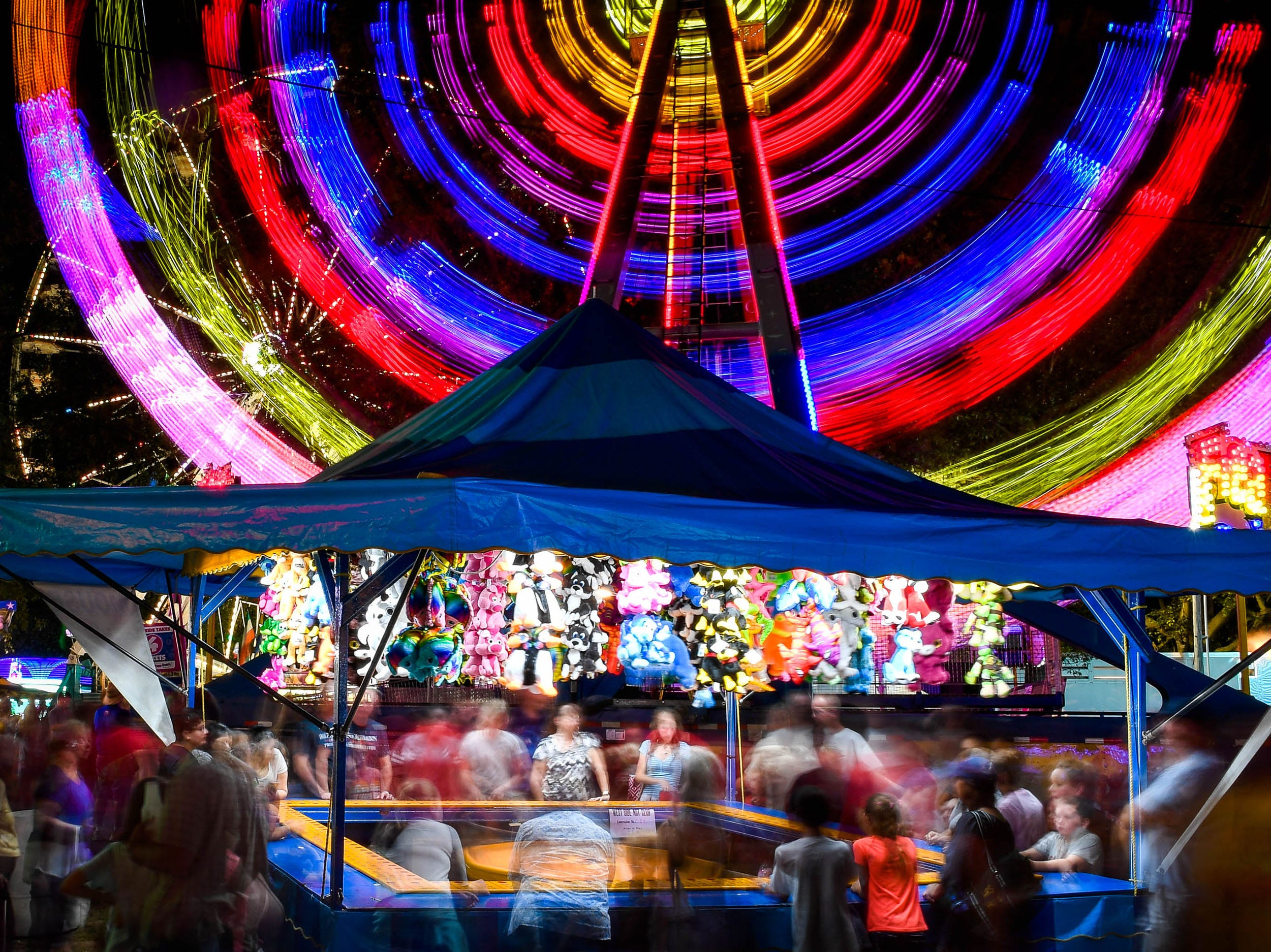 People play carnival games while the Freak Out ride weaves patterns in colored lights in the background of this 15 second time exposure at the West Side Nut Club's Fall Festival Wednesday, October 3, 2018.