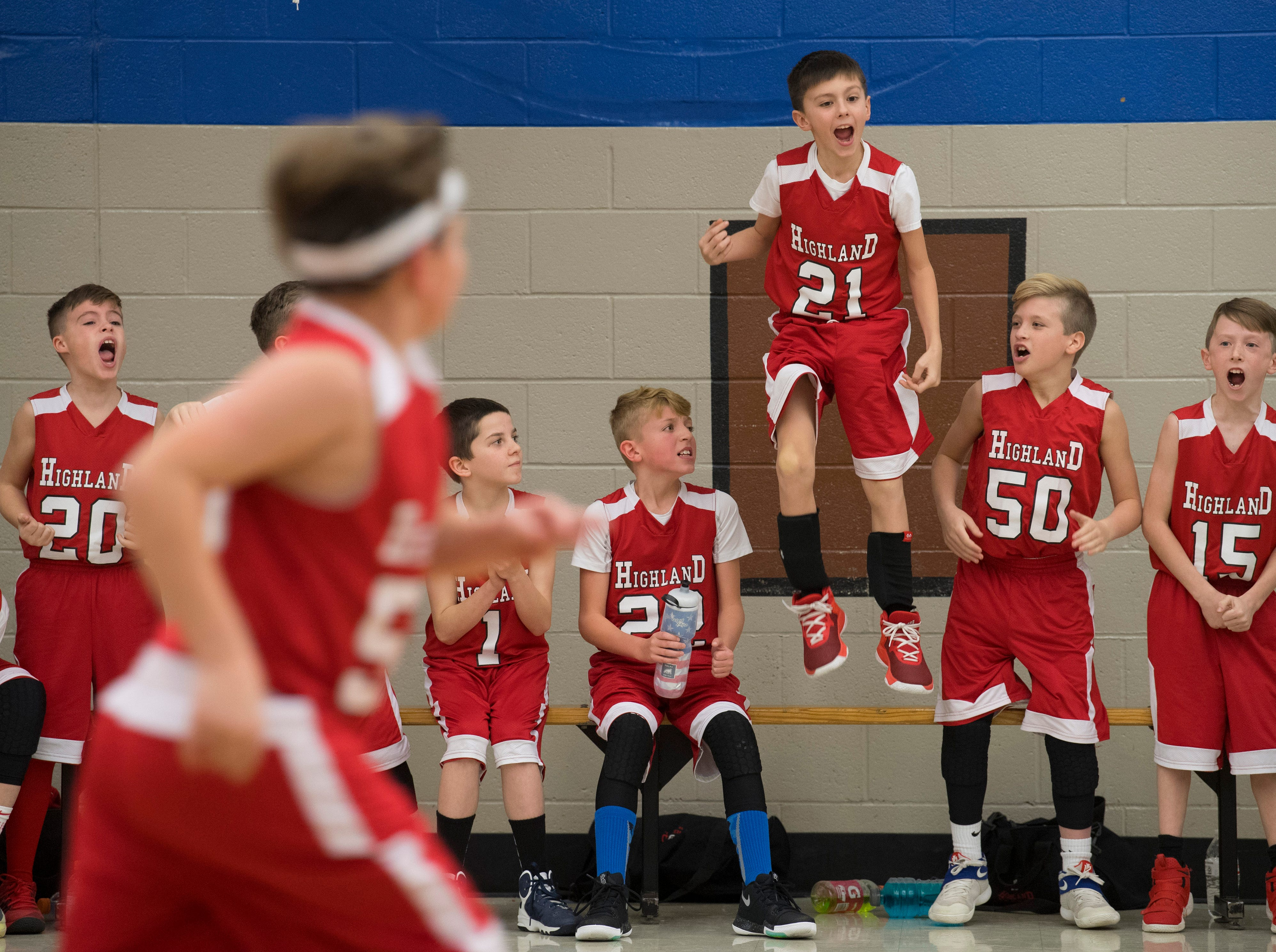 The Highland Highlanders fifth-grade basketball team's bench erupts after taking a one point lead in the final seconds of their game against the Stringtown Chargers at Stringtown Elementary School Monday evening. The Highlanders came out on top 27-26 in the nail-biter of a game.