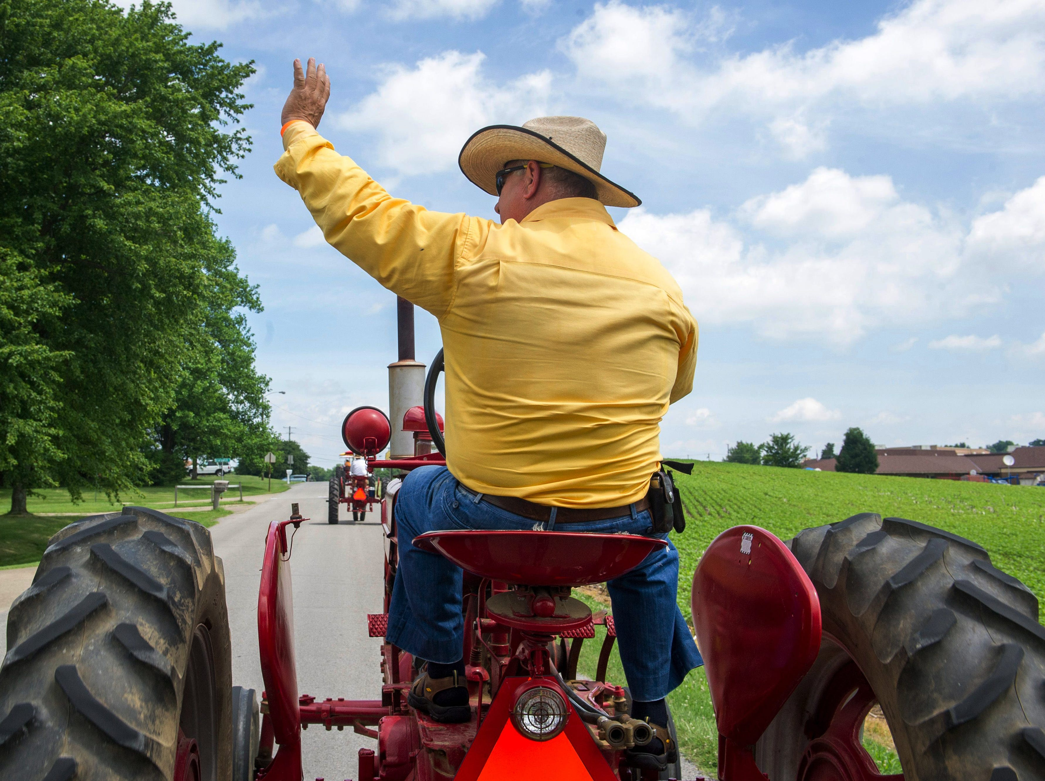 Rick Clements waves to spectators off Kentucky 351 while driving a Farmall M during the 11th annual Shake, Rattle & Roll tractor drive and parade on Sunday, June 24.