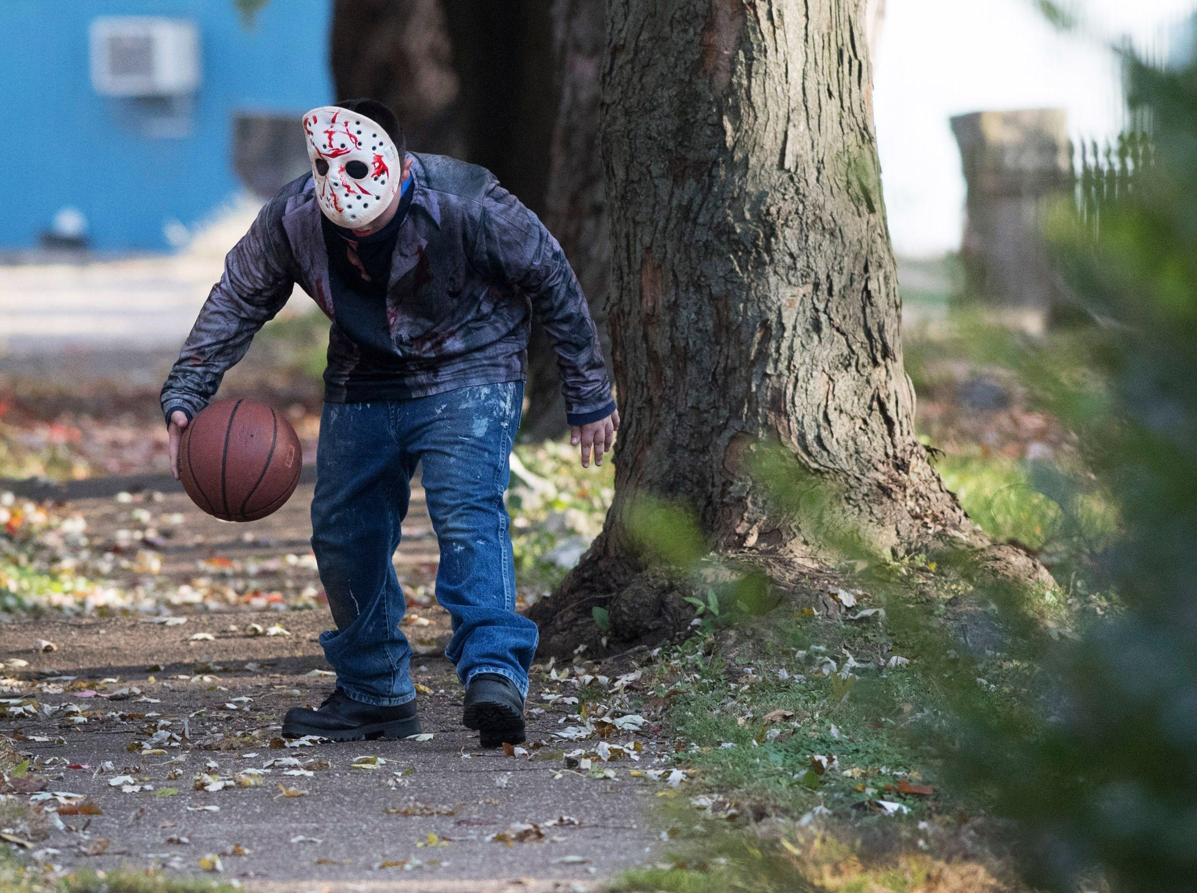 Micheal Blais dressed as Jason Voorhees dribbles a basketball before heading out to trick-or-treat Tuesday, Oct. 30, 2018.