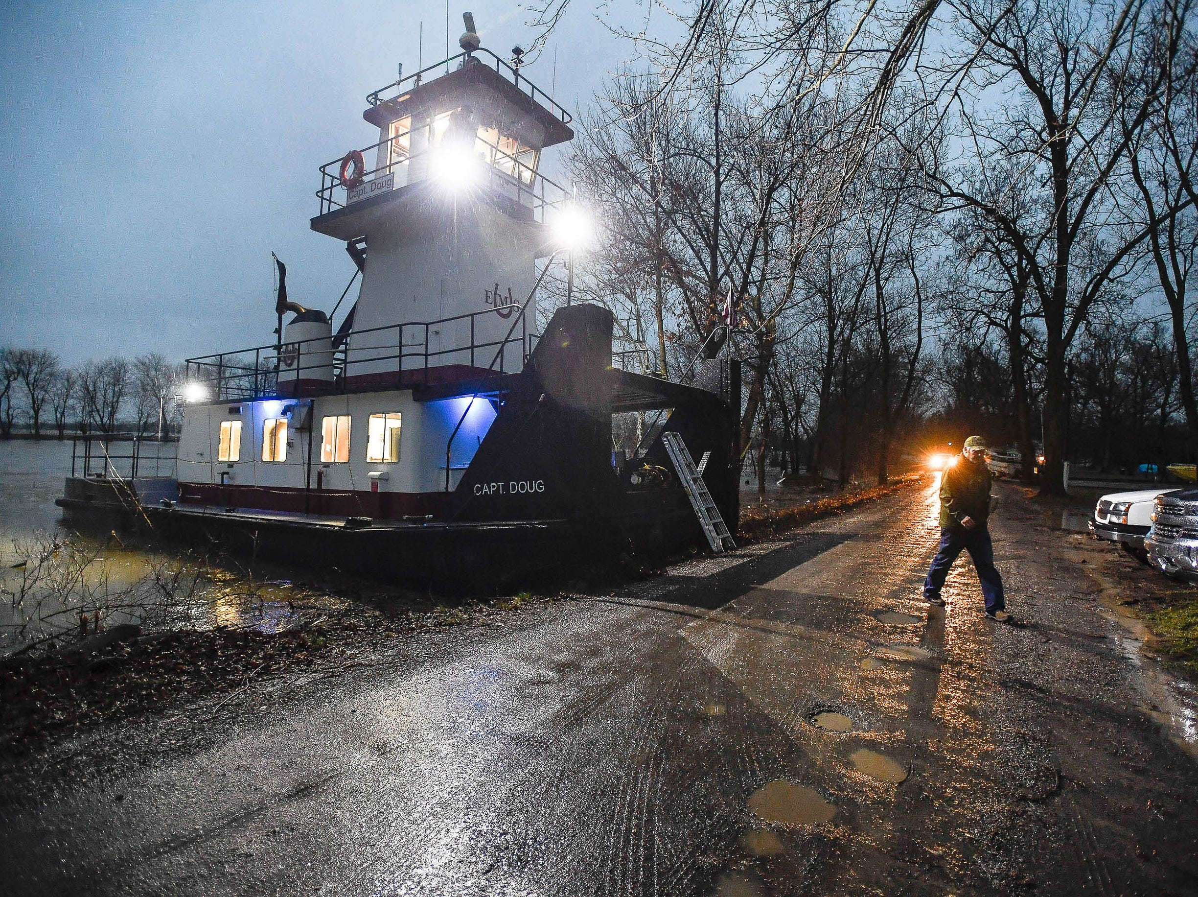The rivers are rising, crewman Nathan Ligon with the towboat Capt. Doug from Evansville Marine Service uses Henderson's Green River Road #1 for a landing because the road to their service dock is flooded by the Green River Wednesday, February 21, 2018.