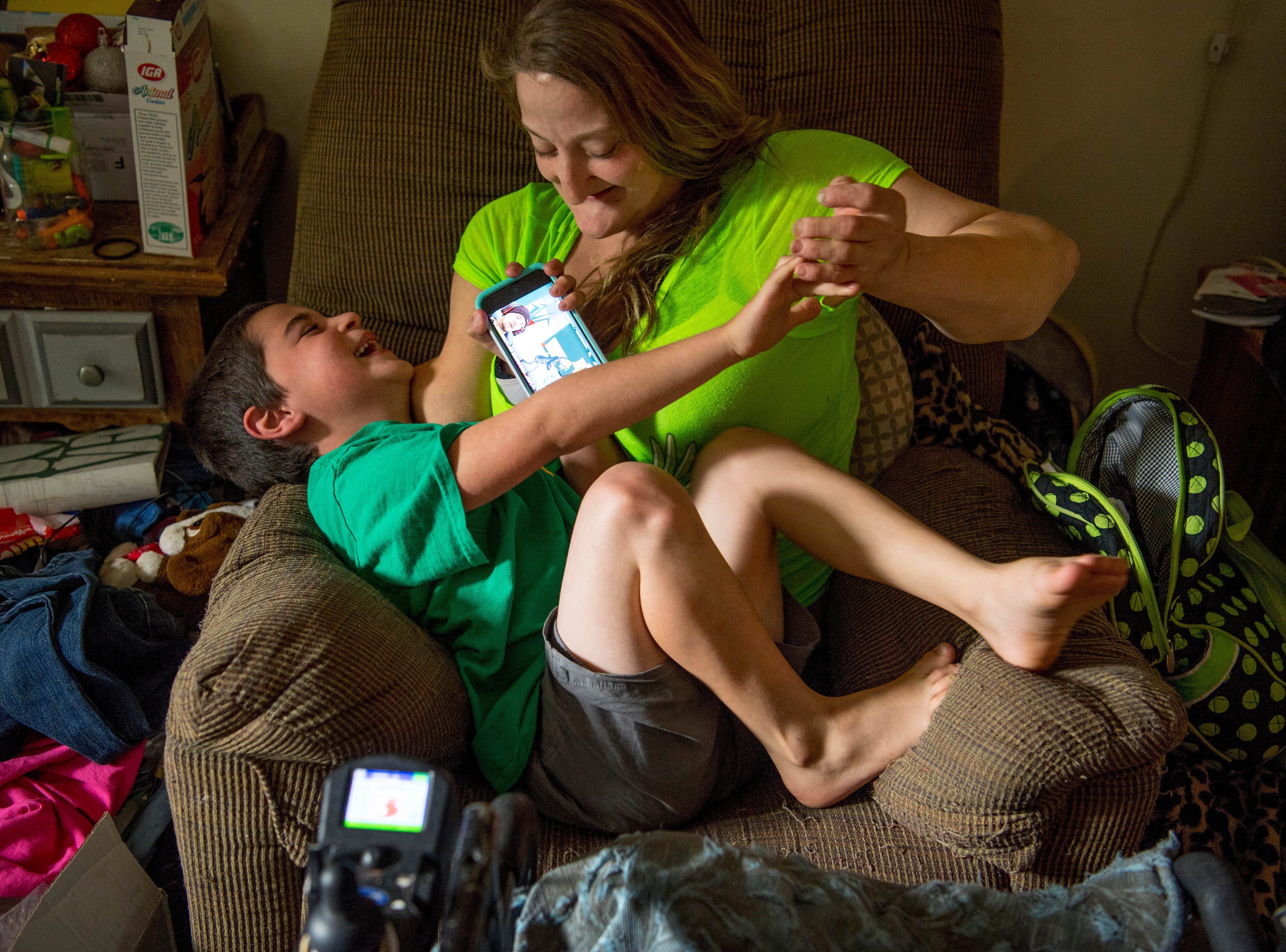A tickle fight breaks out between Leland Smith, 6, and his mom, Amanda, as he tries to watch videos on her cell phone.