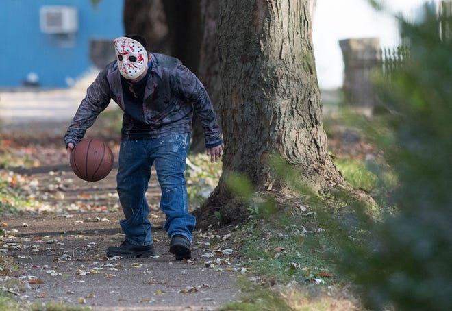 Michael Blais dressed as Jason Voorhees dribbles a basketball before heading out to trick-or-treat Tuesday, Oct. 30, 2018.