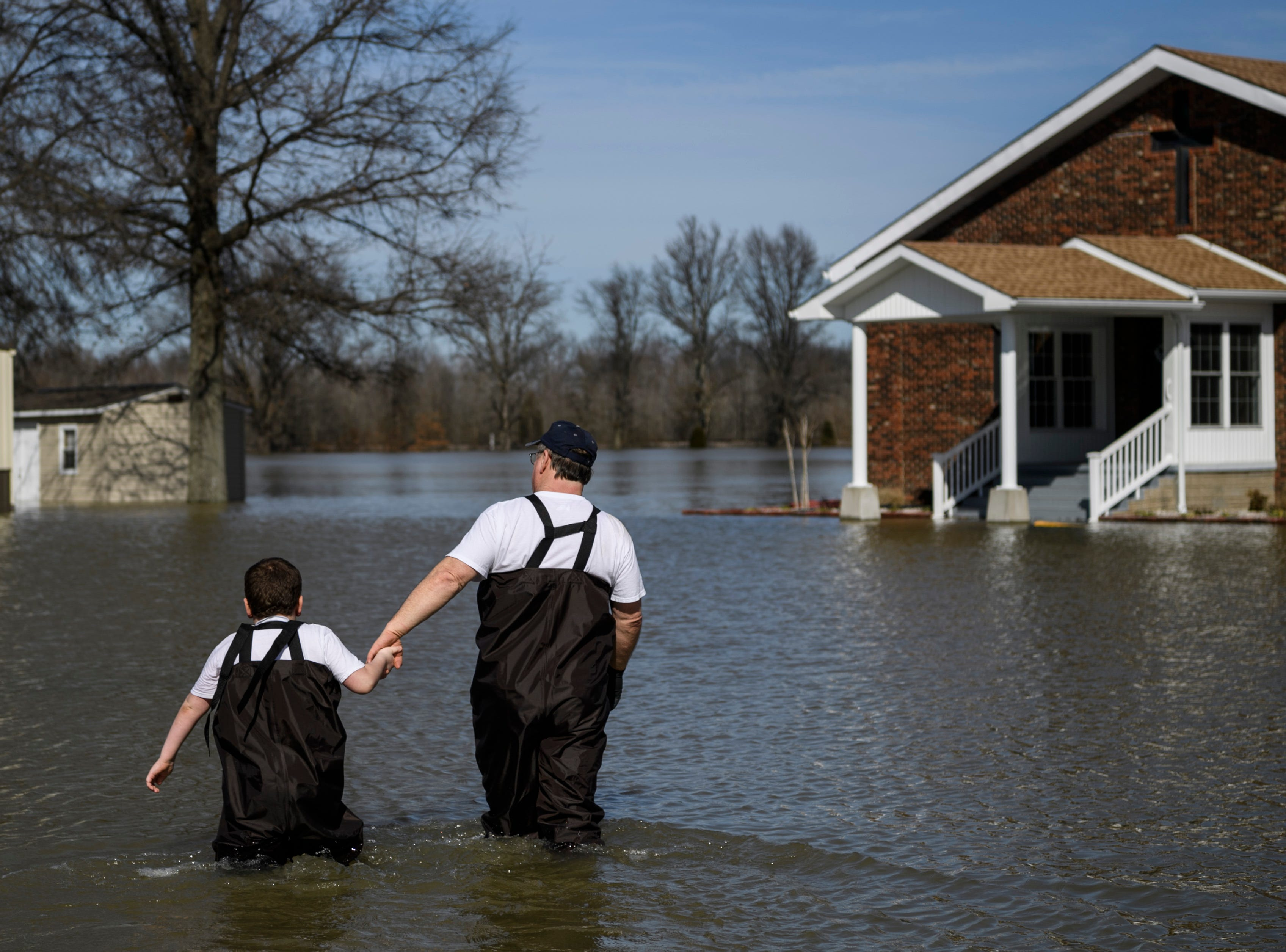 Gabriel Skaggs, 7, and Rev. Barry Skaggs wade through flood water between their home (left) and Beals Pentecost Church (right), where Barry is a pastor, in Reed, Kentucky, Tuesday, Feb. 27, 2018. Gabriel spent time playing in the water around his home and didn't miss any school days because he is home-schooled.
