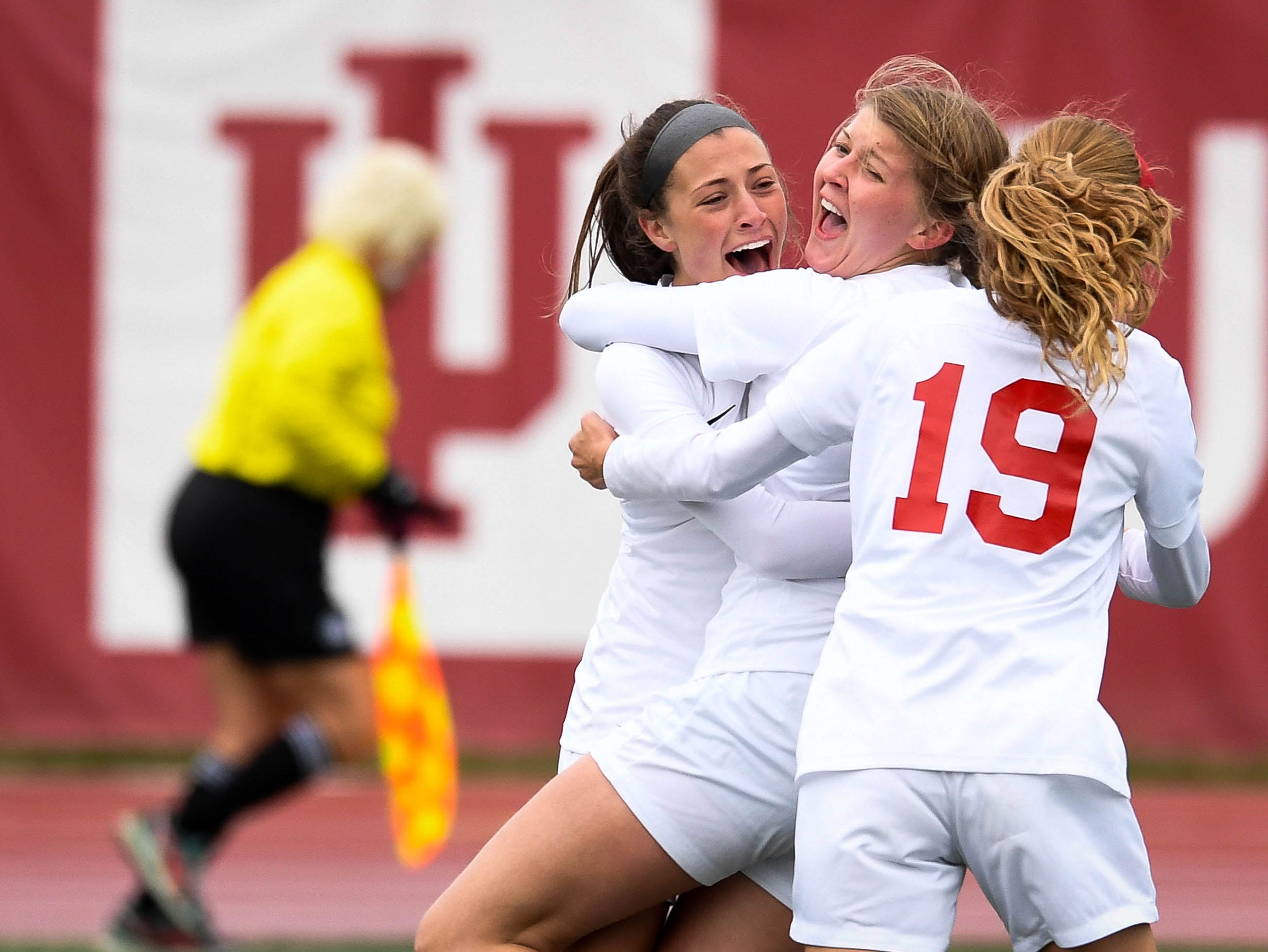 Mater Dei's Ellsa Bonnell (1) and Miranda Nosko (19) congratulate Mater Dei's Maddie Folz (14) for her game winning goal as the defending state champions Mater Dei Wildcats play the Wheeler Bearcats in the Class 1A state championship game in Indianapolis Saturday, October 27, 2018.