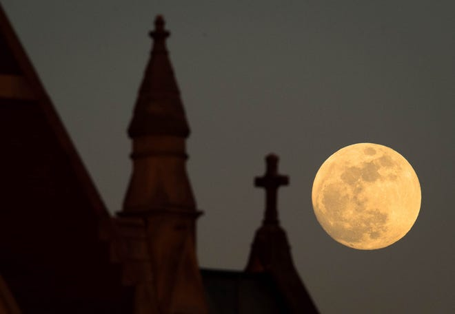 "Super Blue Blood Moon rising above Henderson's Holy Name of Jesus Catholic Church Tuesday evening. According to NASA the ""super moons"" are when the moon is closer to Earth in it's orbit, known as perigee. It is also the second full moon of the month, commonly known as a ""blue moon"" and early Wednesday morning a total lunar eclipse occurred giving it a reddish tint, known as a ""blood moon.""  It will be twenty years before this combination occurs again, January 30, 2018."