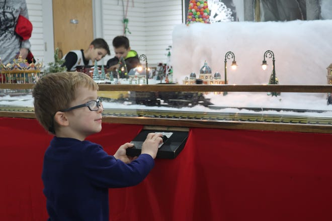 """Visitors to the Hayes Presidential Library and Museums enjoy the interactive buttons on the """"Hayes Train Special"""" model train display in the museum. This year, nine trains wind through the display, which features a candy land theme."""