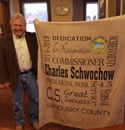 Sandusky County Commissioner Charlie Schwochow is given a blanket by staff for his more than four years of service as county commissioner.