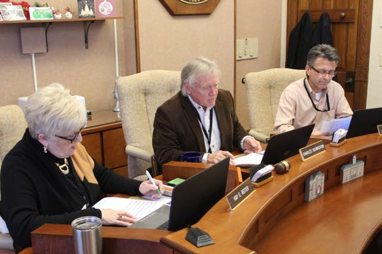 Sandusky County Commissioner Charlie Schwochow, middle, flanked by commissioners Kay Reiter and Scott Miller, makes one final motion to adjourn Thursday during his last meeting.