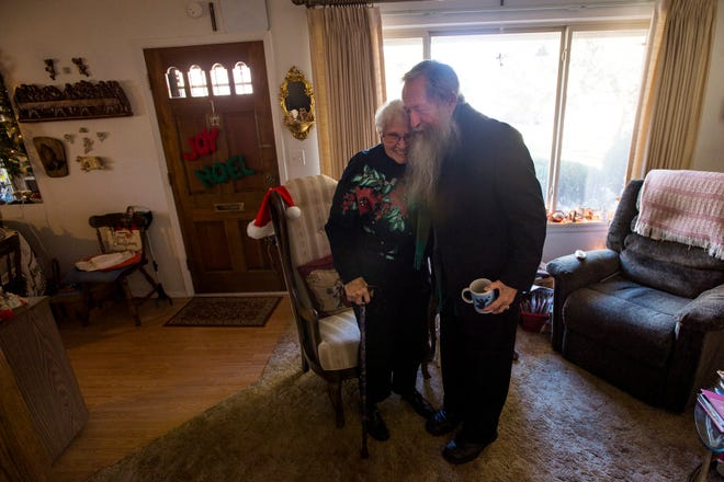 Father Don Willette hugs his former secretary Arlene Miller after stopping by her home for a visit on Thursday, Dec. 27, 2018, in Fort Collins, Colo.