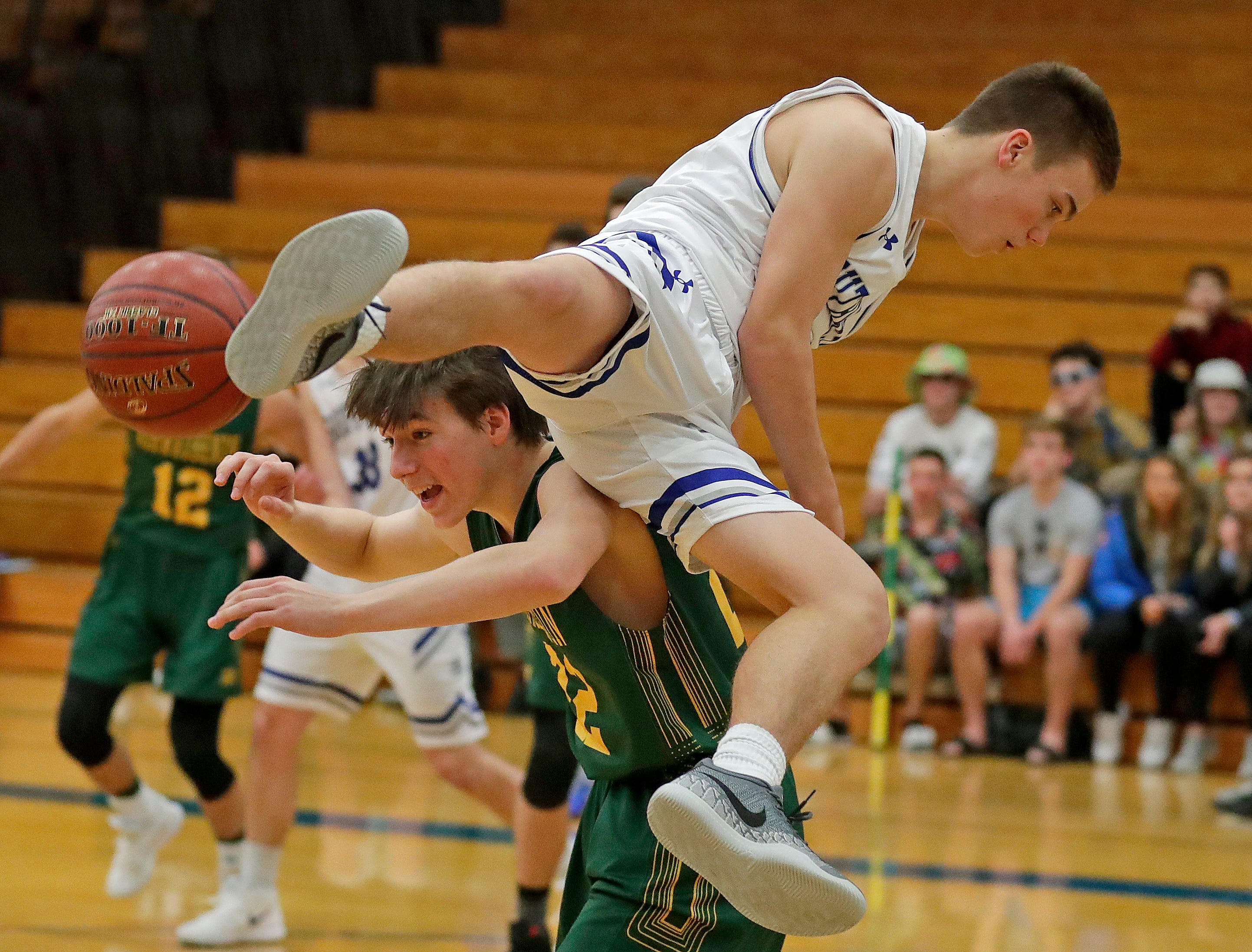 Southwest's Owen Stieber lands on top of Ashwaubenon High School's Christopher Morgan during FRCC basketball action  Tuesday, December 11, 2018 at Southwest High School in Green Bay, Wis.