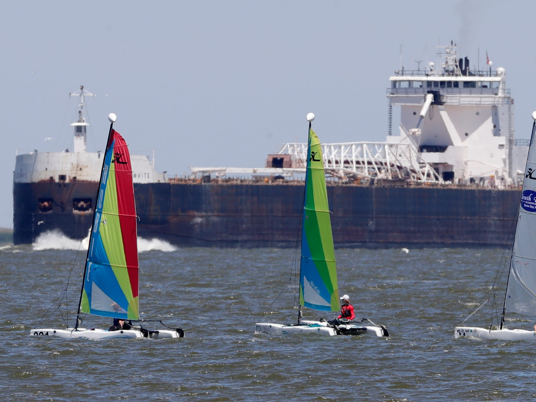 Laser sailboats round the mark as a freighter heads into the Port of Green Bay