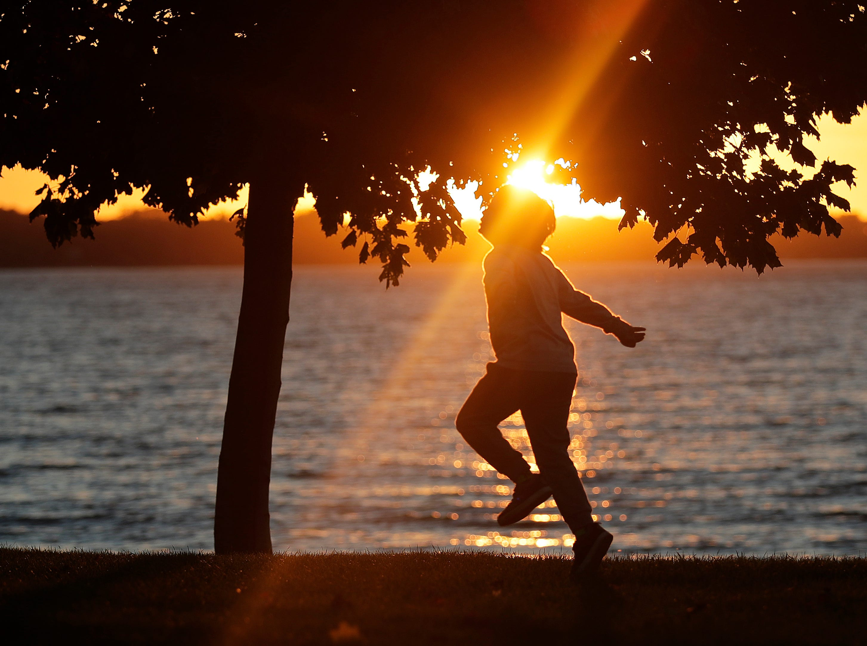 Arlo Eggert, 7, of Green Bay frolics beneath a tree as the sun sets over the bay of Green Bay at Communiversity Park Thursday, October 18, 2018 in Green Bay, Wis