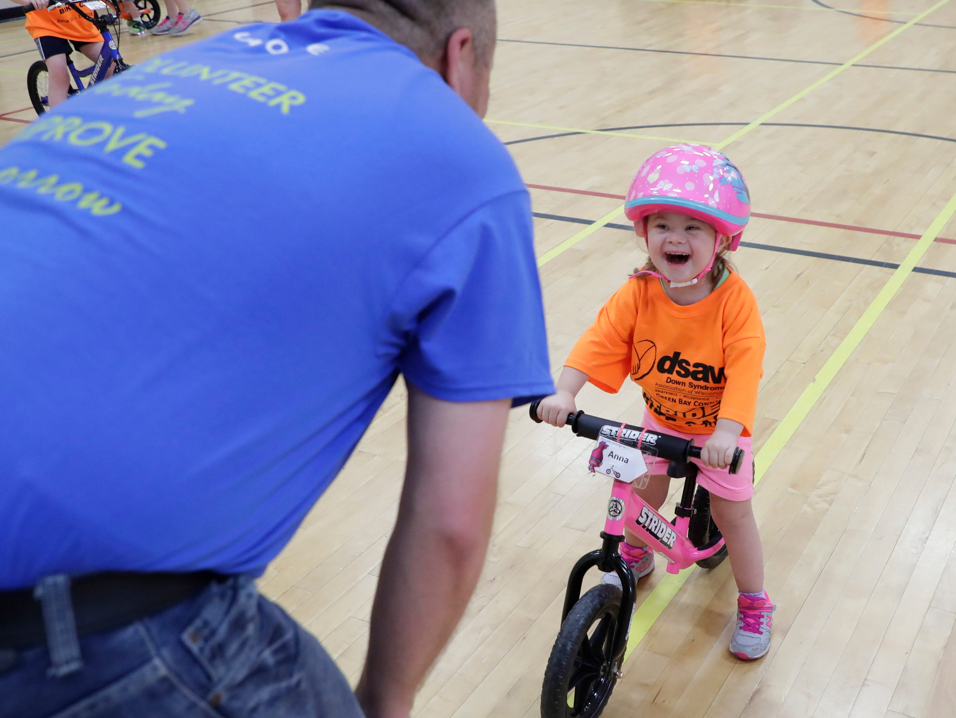 Anna smiles at volunteer Clint Smith during the Down Syndrome Association of Wisconsin Strider Bike training at the East Side YMCA Monday, June 11, 2018 in Bellevue, Wis.