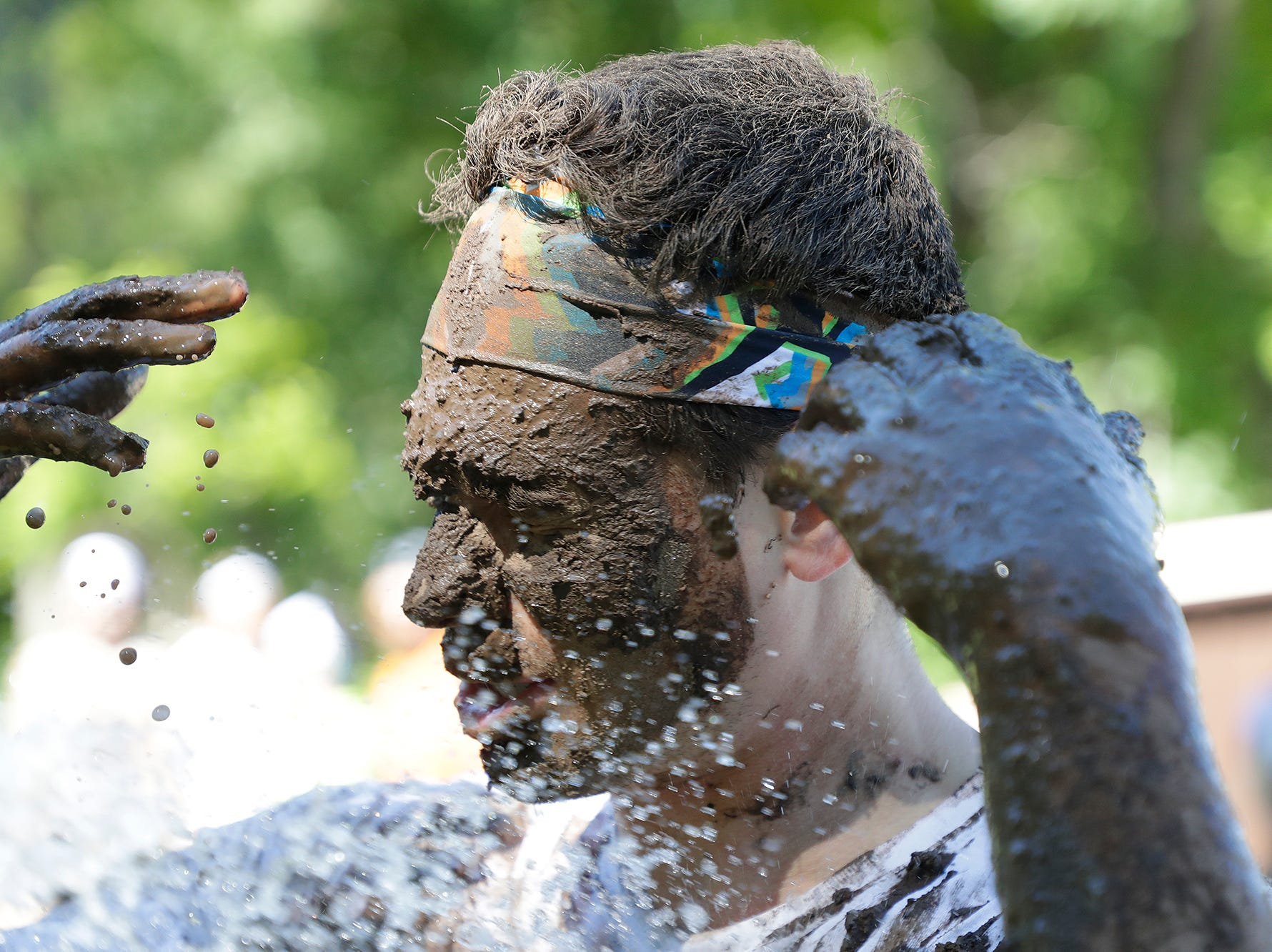 The first annual Crazy Mud Mayhem Obstacle course run at Triangle Sports Park and Baird Creek park Saturday, June 23, 2018 in Green Bay, Wis. Nate Stewart of Green Bay gets hosed off after immersing himself in the experience.