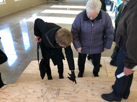 Holy Trinity parishioners look at some of the signatures of members on subflooring around the altar of the new church during a tour on Dec. 15-16.