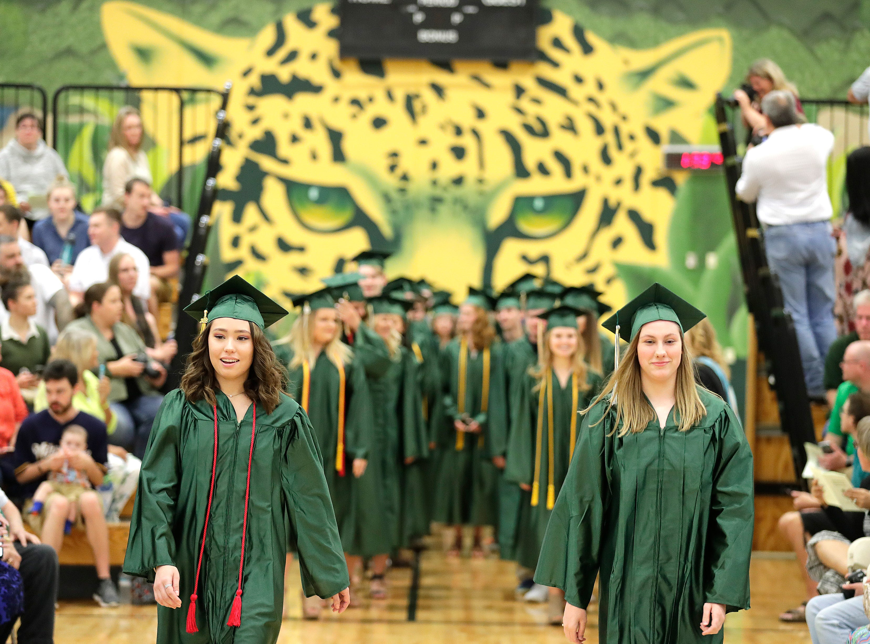 Ashwaubenon High School graduating students walk into graduation ceremonies Sunday, June 3, 2018 in Ashwaubenon, Wis.