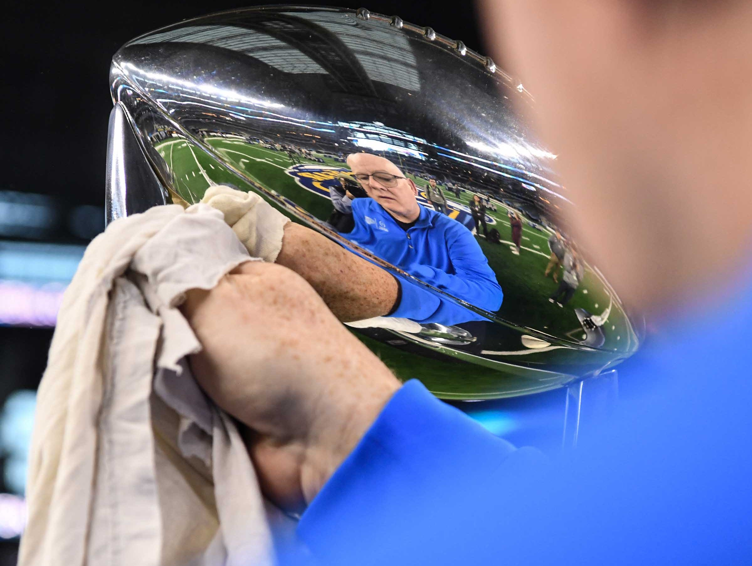 Marty MacInnis of the Cotton Bowl polishes the game trophy during Media Day for Clemson and Notre Dame at the AT&T Stadium in Dallas December 27, 2018.