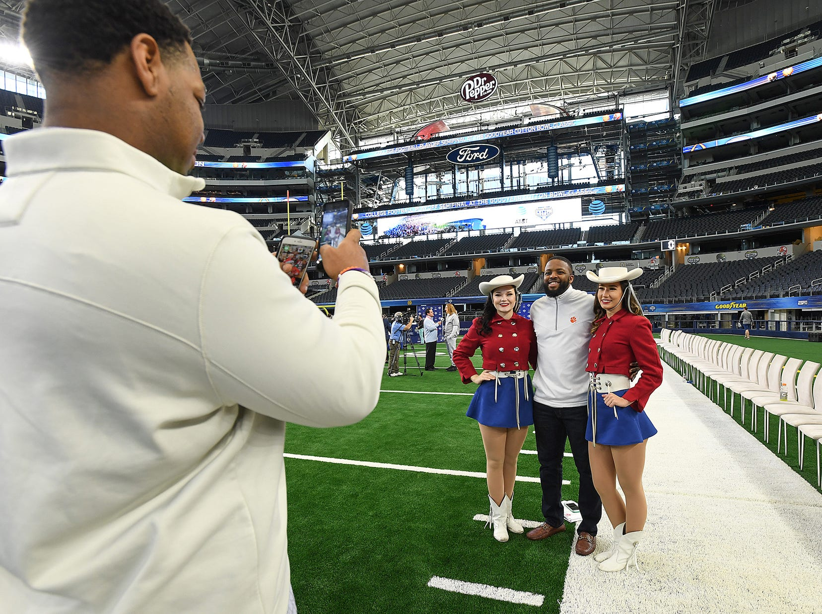 Clemson grad assistant Deandre McDaniel poses with cow girls during the Tigers Cotton Bowl media day at AT&T Stadium in Arlington, TX Thursday, December 27, 2018.