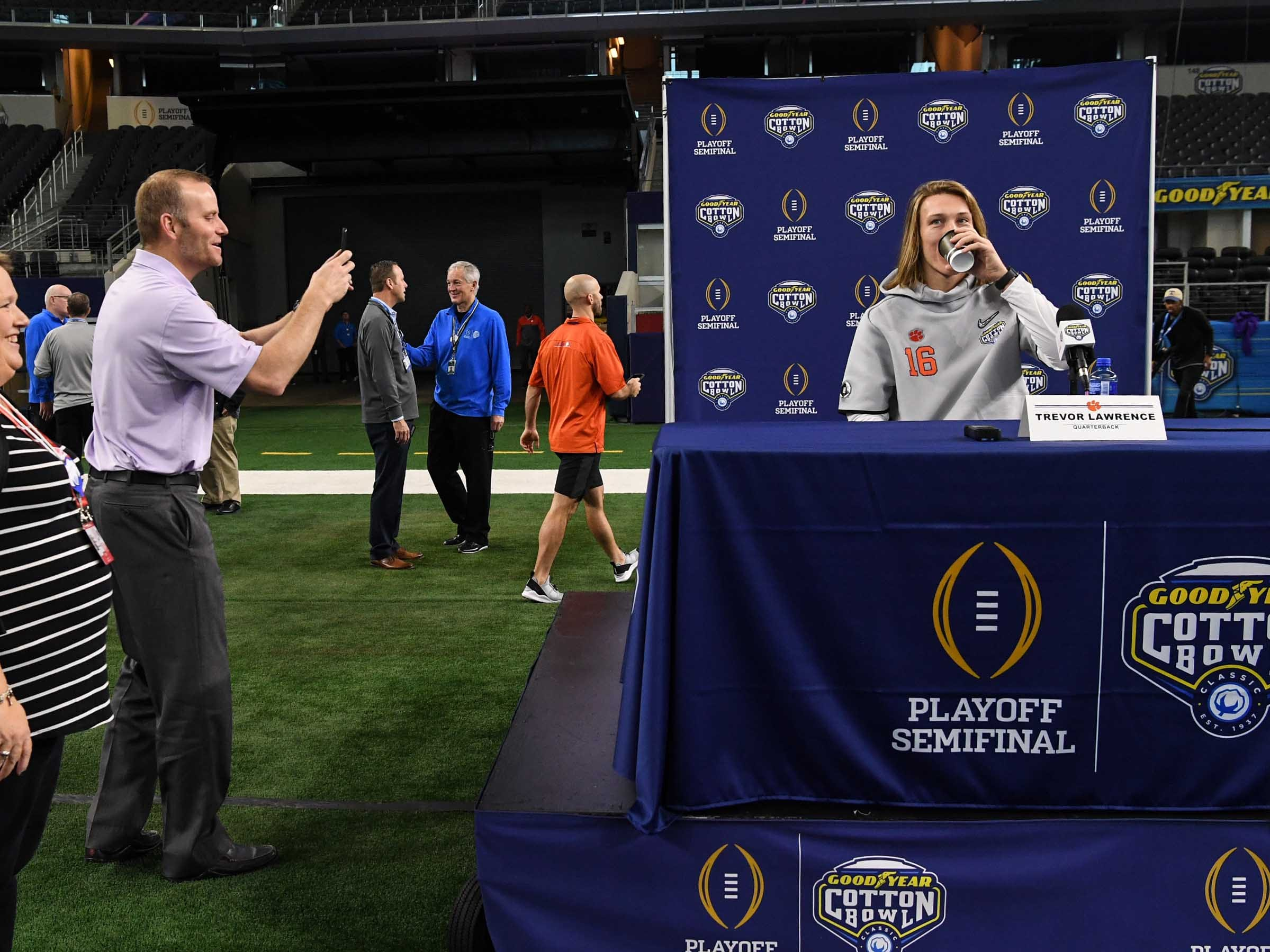 Clemson quarterbacks coach Brandon Streeter, left, takes a photo of quarterback Trevor Lawrence during Media Day for Clemson and Notre Dame at the AT&T Stadium in Dallas December 27, 2018.