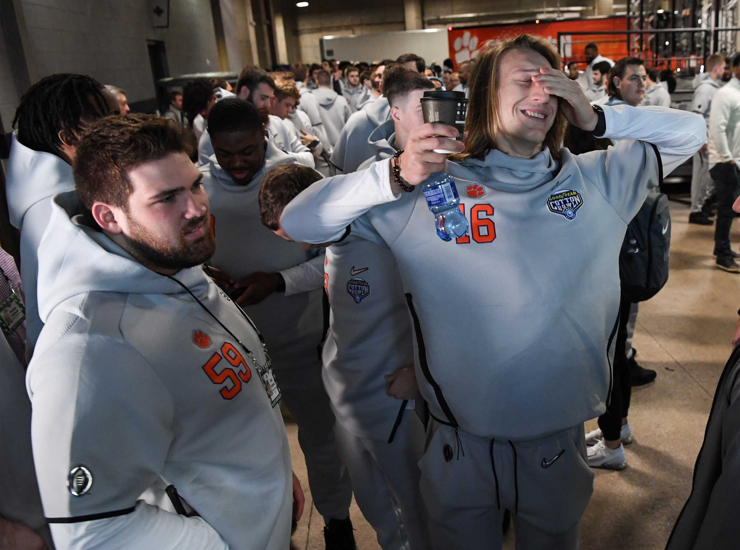 Clemson quarterback Trevor Lawrence, right, stretches near offensive lineman Gage Cervenka, left, before entering Media Day for Clemson and Notre Dame at the AT&T Stadium in Dallas December 27, 2018.