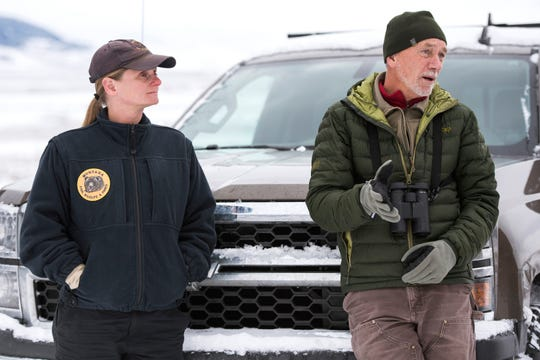 In this Friday, Dec. 14, 2018 photo Montana Fish, Wildlife and Parks Biologist Julie Cunningham and Bob Garrott, a Montana State professor and biologist, discuss the transplant of some bighorn sheep from the herd near Quake Lake to Wolf Creek south of Cameron, Mont. Cunningham, who has worked for FWP for 12 years, is the person in charge of the sheep herd that lives near Quake Lake, known as the Taylor-Hilgards herd.