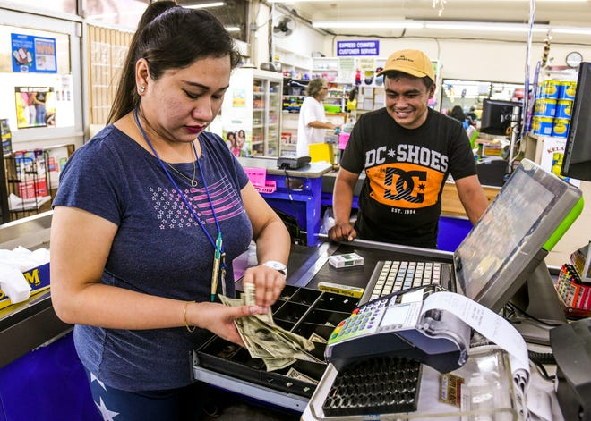 Cashier Sara Muldong gathers the correct change during a purchase by customer Eric Crisolo Suarez at the Super Mart store in Mangilao on Thursday, Dec. 27, 2018.