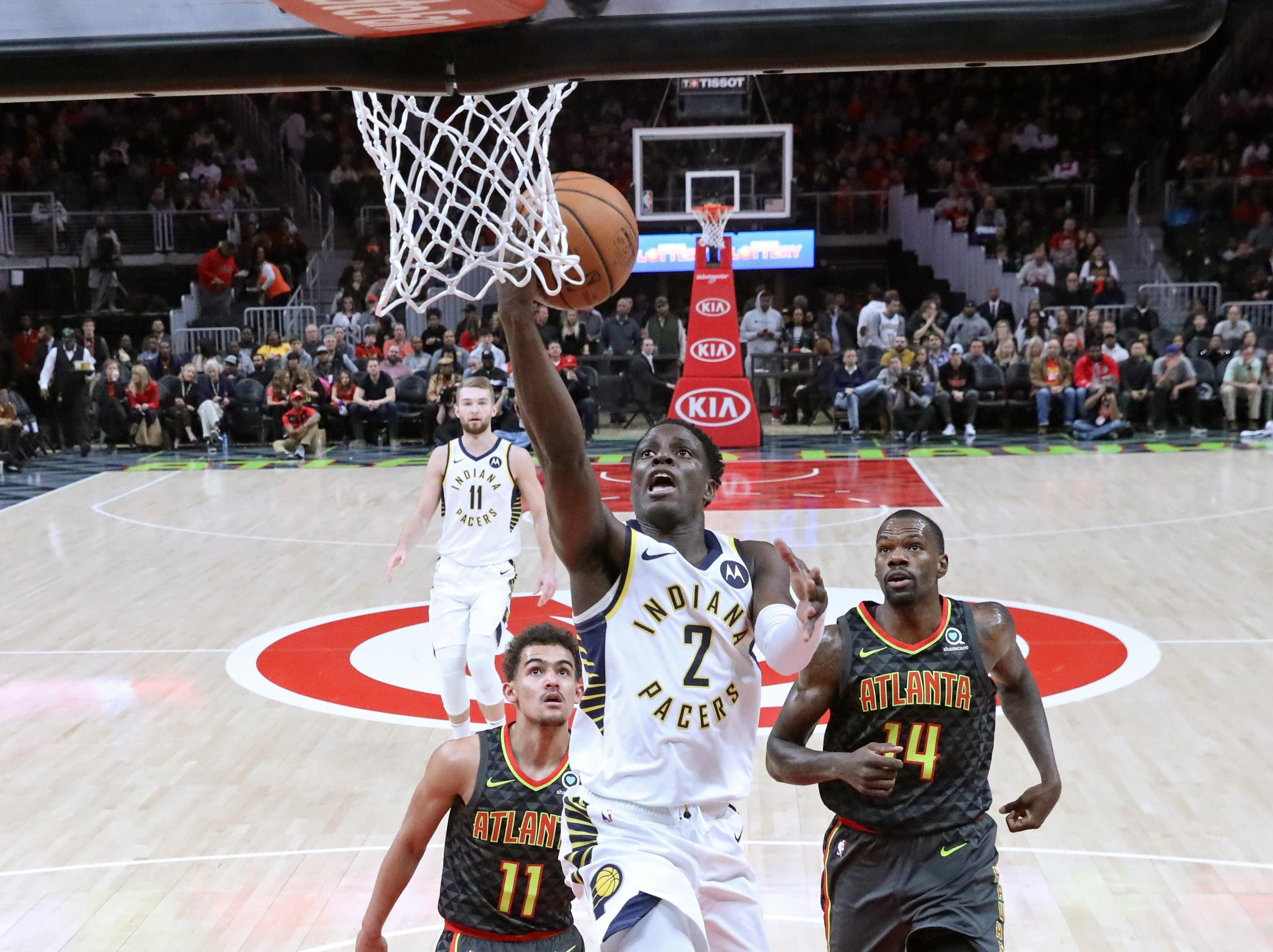 Dec 26, 2018; Atlanta, GA, USA; Indiana Pacers guard Darren Collison (2) attempts a layup against Atlanta Hawks guard Trae Young (11) and center Dewayne Dedmon (14) in the first quarter at State Farm Arena. Mandatory Credit: Jason Getz-USA TODAY Sports