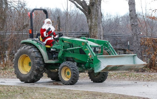 Santa makes his grand entrance on a tractor during Santa's annual visit to Wolf Park in Battle Ground Indiana on Saturday, Dec. 15, 2018.