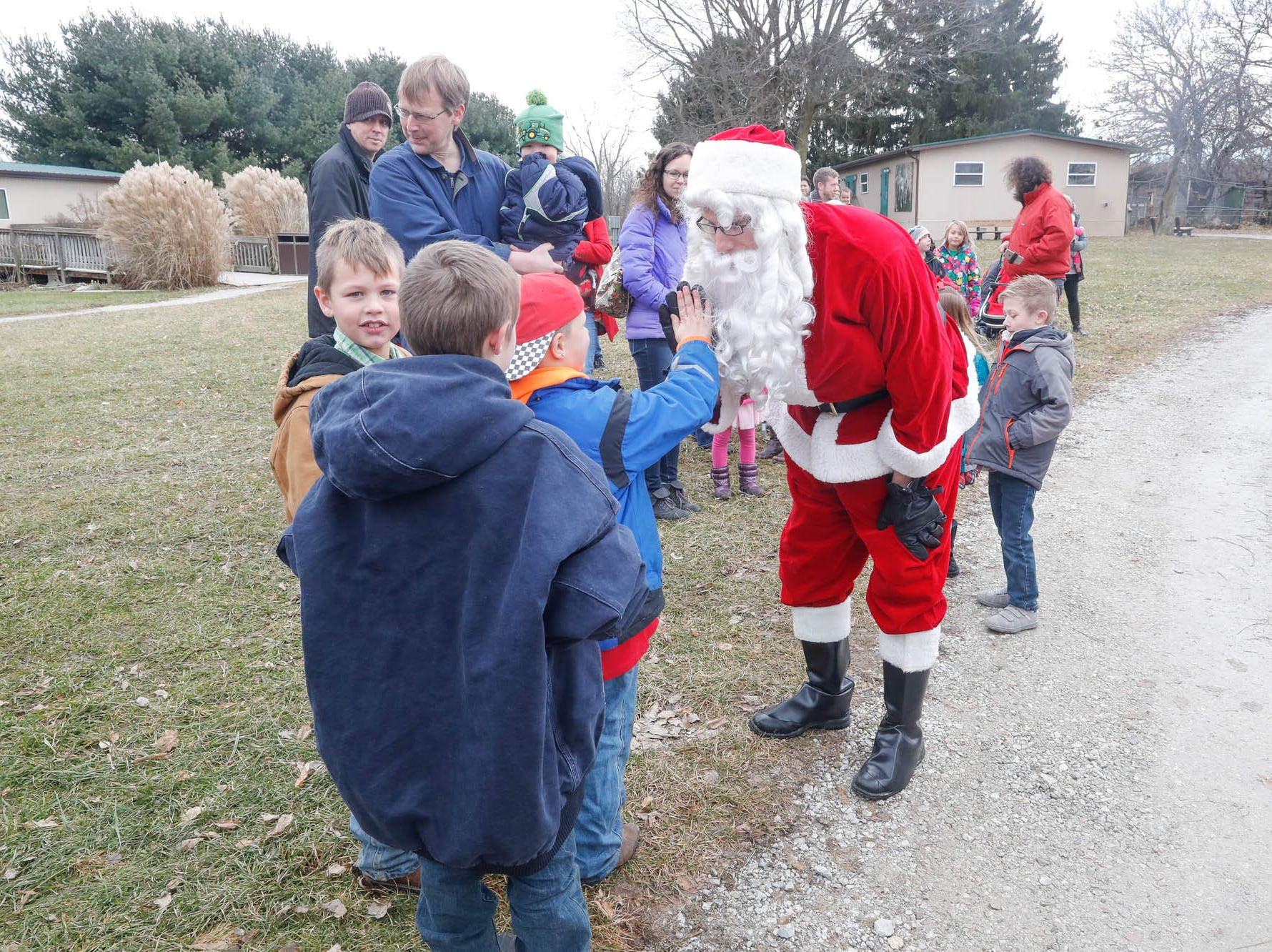 Santa high fives a little guest during his visit to Wolf Park in Battle Ground Indiana on Saturday, Dec. 15, 2018.