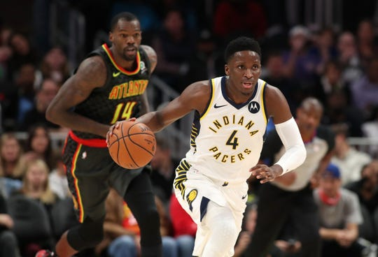 Pacers guard Victor Oladipo (4) pushes the ball up the court ahead of Atlanta Hawks center Dewayne Dedmon (14) in the first quarter at State Farm Arena.