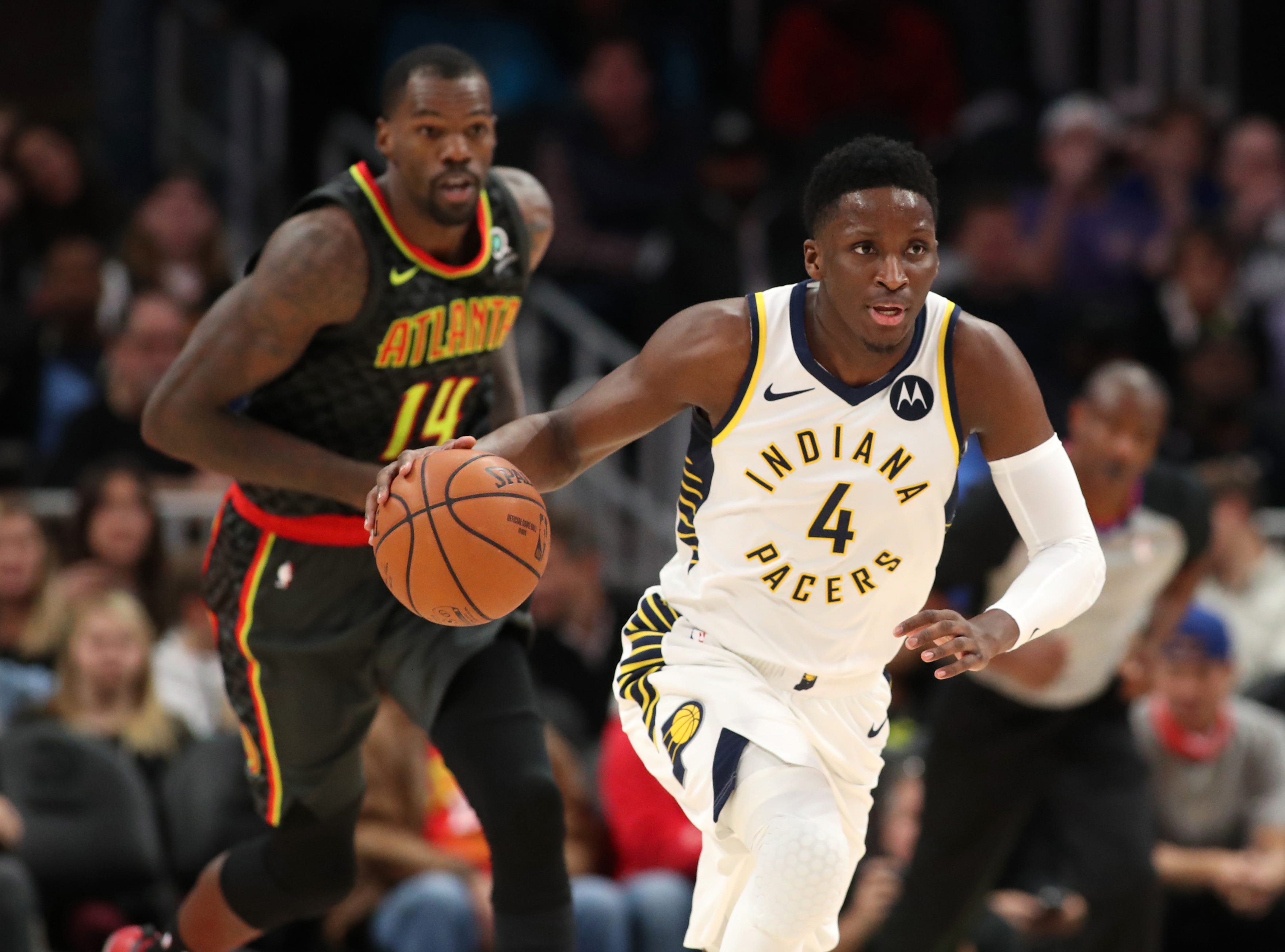 Dec 26, 2018; Atlanta, GA, USA; Indiana Pacers guard Victor Oladipo (4) pushes the ball up the court ahead of Atlanta Hawks center Dewayne Dedmon (14) in the first quarter at State Farm Arena. Mandatory Credit: Jason Getz-USA TODAY Sports