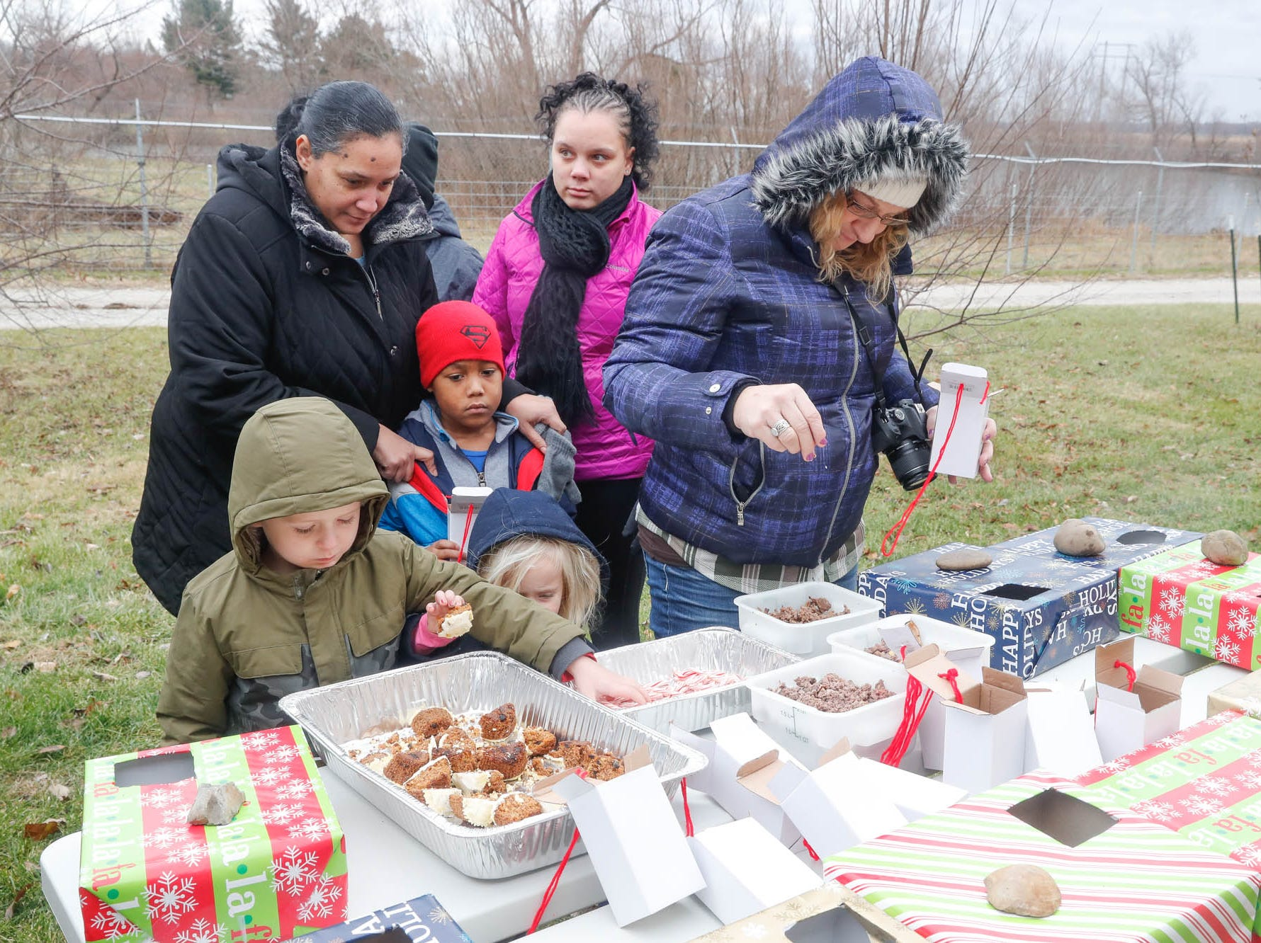 Guests fill gift boxes with Christmas treats for the wolves during Santa's visit to Wolf Park in Battle Ground Indiana on Saturday, Dec. 15, 2018.