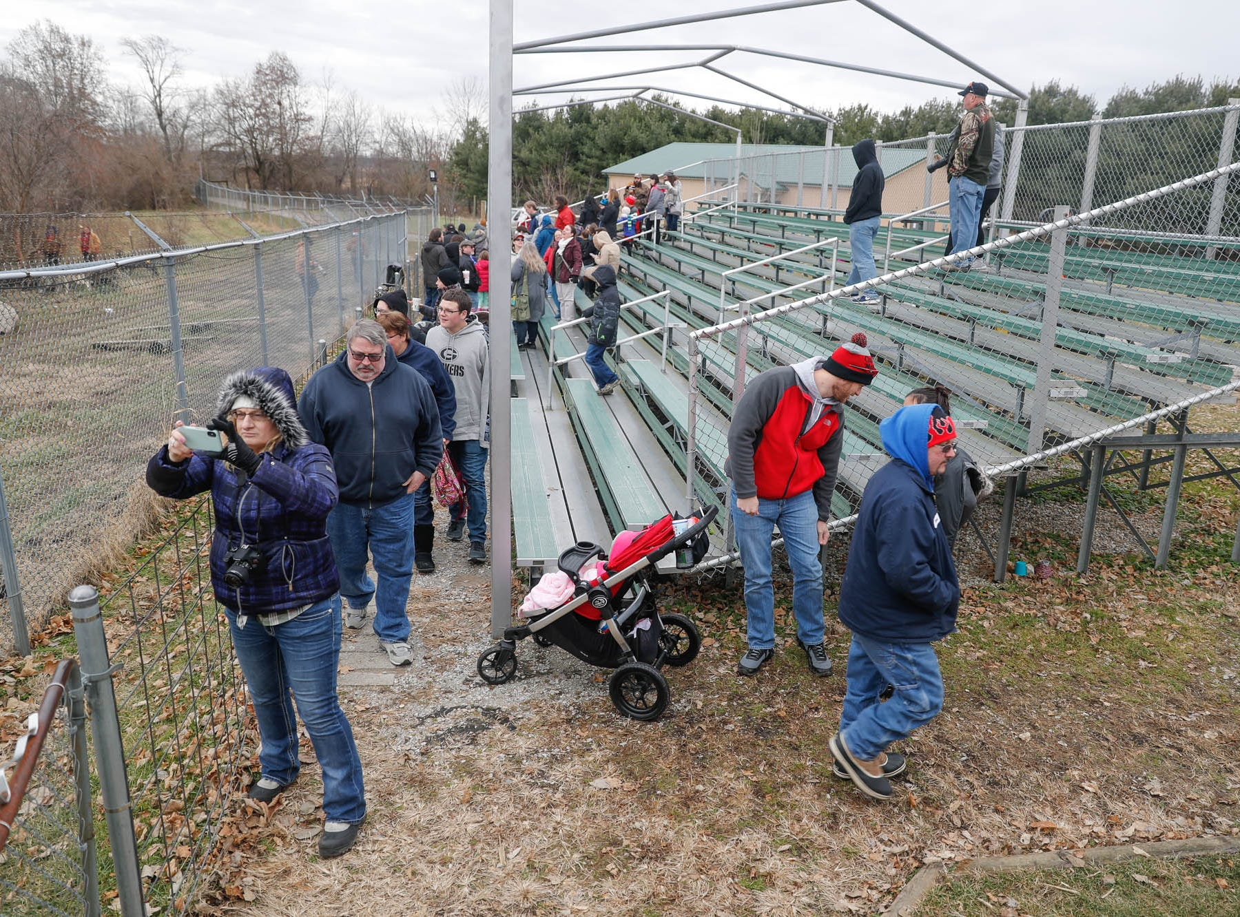 Guests snap photos as they exit the bleachers for a tour during Santa's annual visit to Wolf Park in Battle Ground Indiana on Saturday, Dec. 15, 2018.