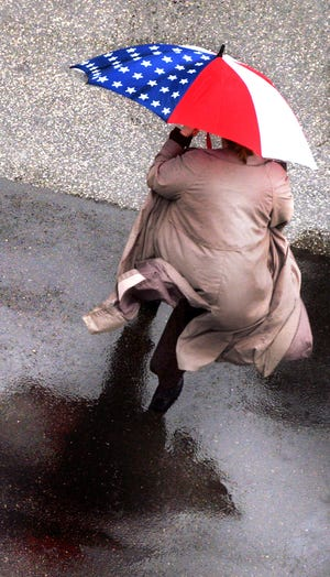 A pedestrian in Downtown Indianapolis holds an umbrella with the stars and stripes motif to fight the cold gusts of wet winter in this December 2003 photo.