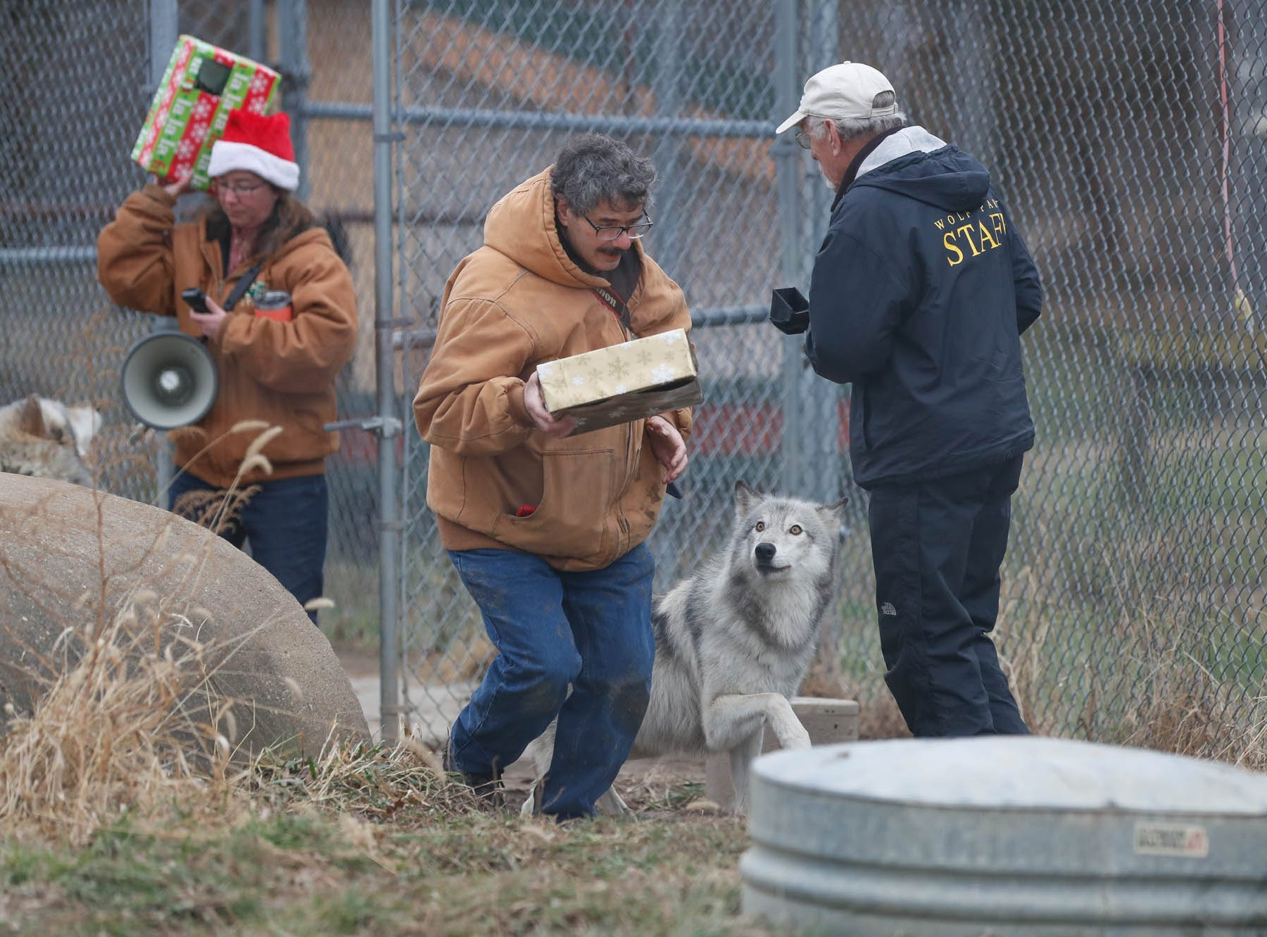 Left to right, Wolf Park Managing Director, Dana Drenzek, left, Park Photographer and Animal Care Staff member, Monty Sloan, and Park Board Member, Tom OÕDowd,  during Santa's visit to Wolf Park in Battle Ground Indiana on Saturday, Dec. 15, 2018.