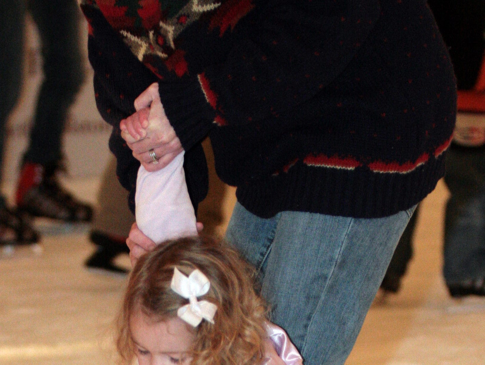 Cadence Horner, 2, tries to keep her footing with help from her mother Niki Horner while ice skating during the New Year's eve on Market Square celebration on Monday.
