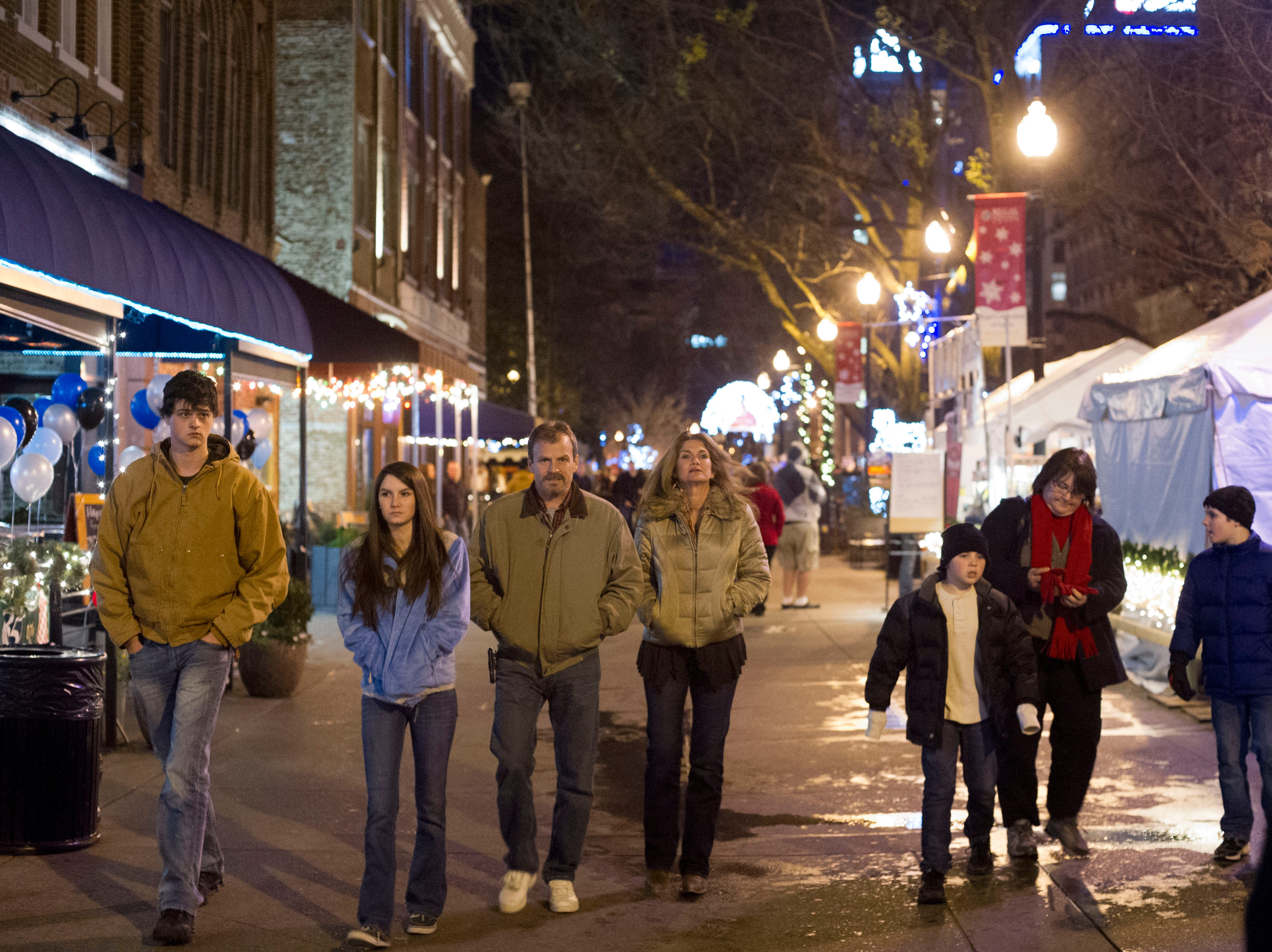 People walk Market Square on New Year's Eve on Monday, December 31, 2012.