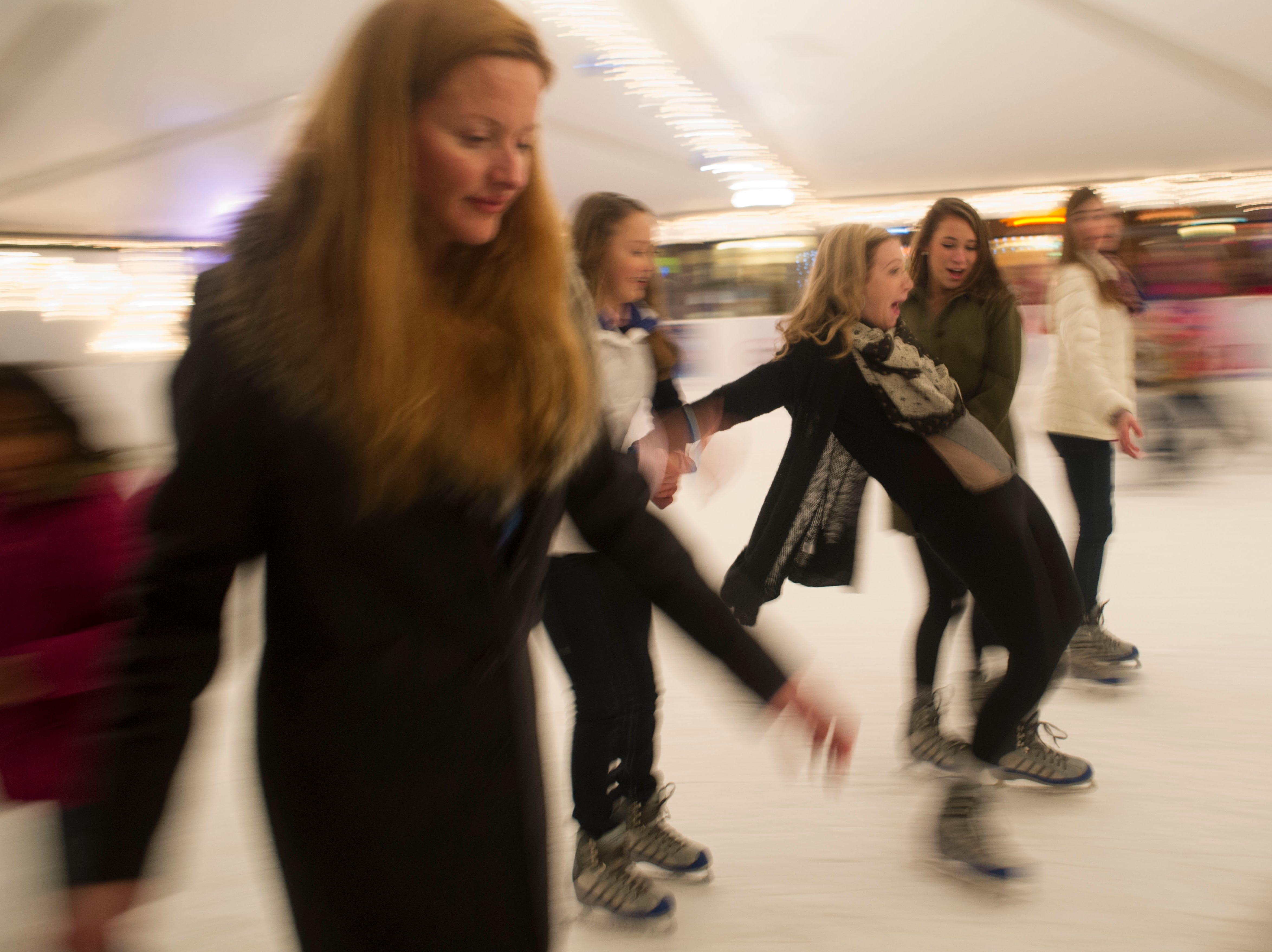Skaters try to keep their balance while ice staking at Holidays on Ice. The ice rink is staying open until midnight as part of the New Year's Eve celebration on Monday, December 31, 2012.