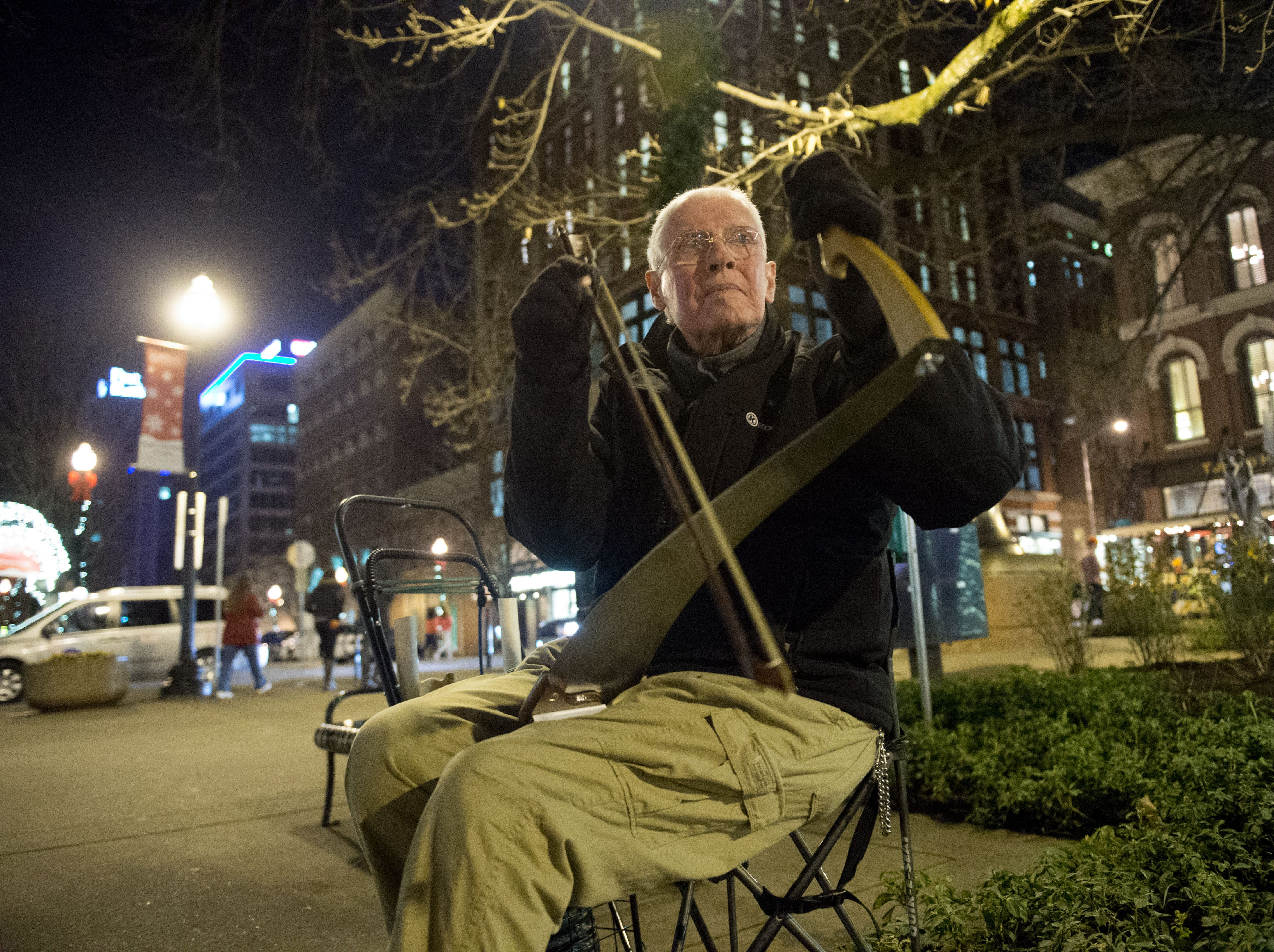 Bob Maddox plays a musical saw at Market Square on New Year's Eve on Wednesday, December 31, 2014.